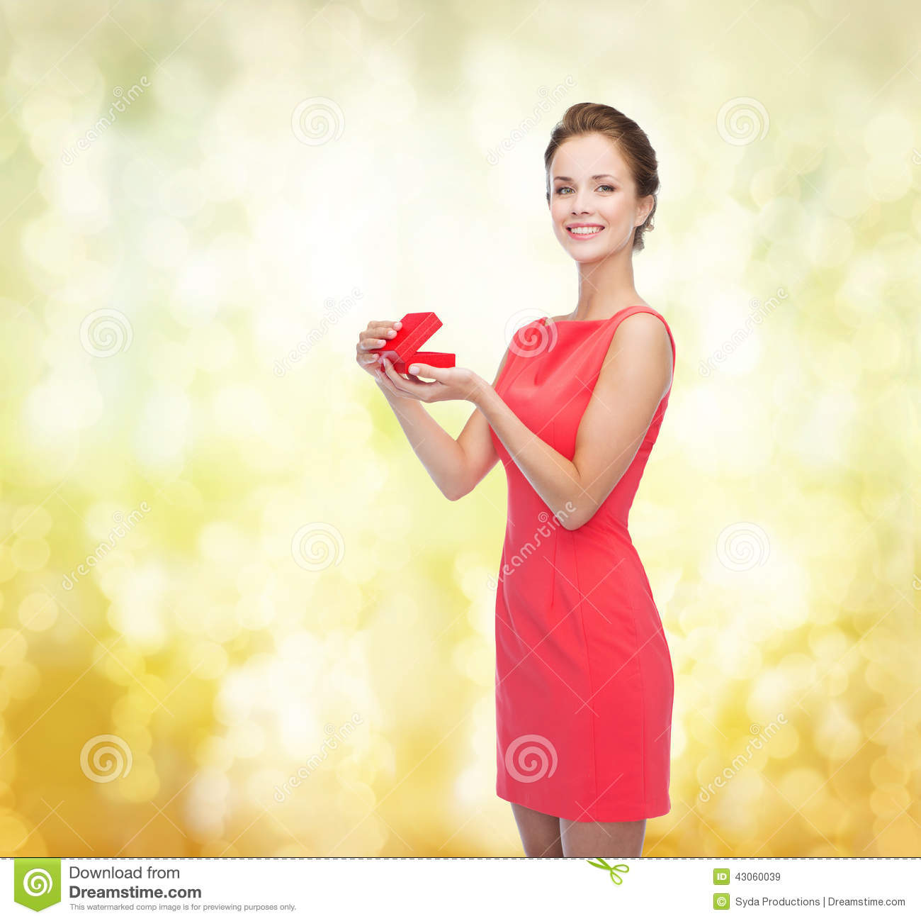 Celebration concept smiling young woman in red dress with gift box