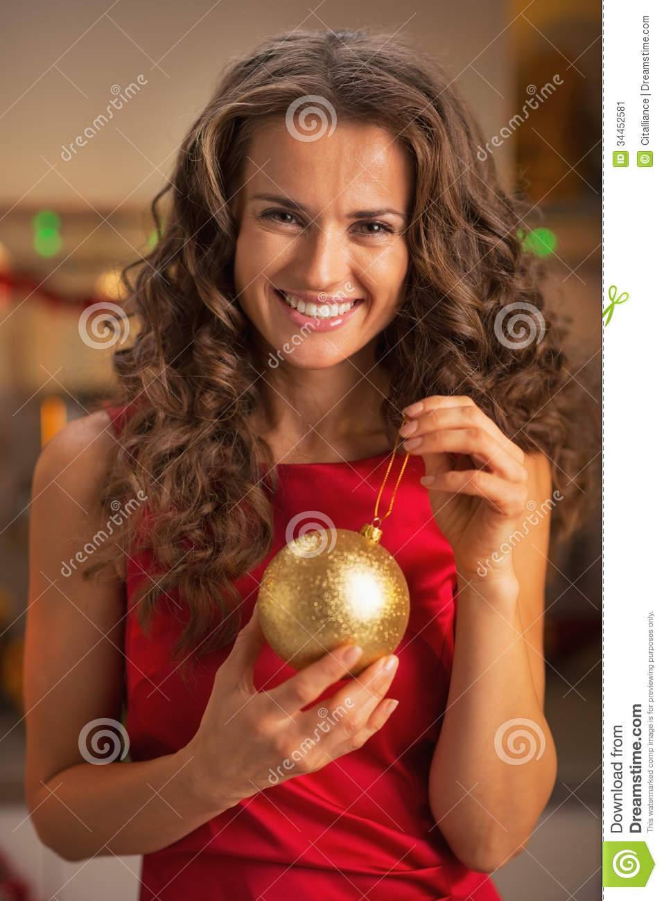 Smiling young woman in red dress holding christmas ball stock image