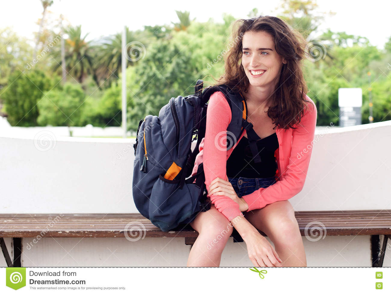 Smiling young woman sitting on a bench waiting with backpack