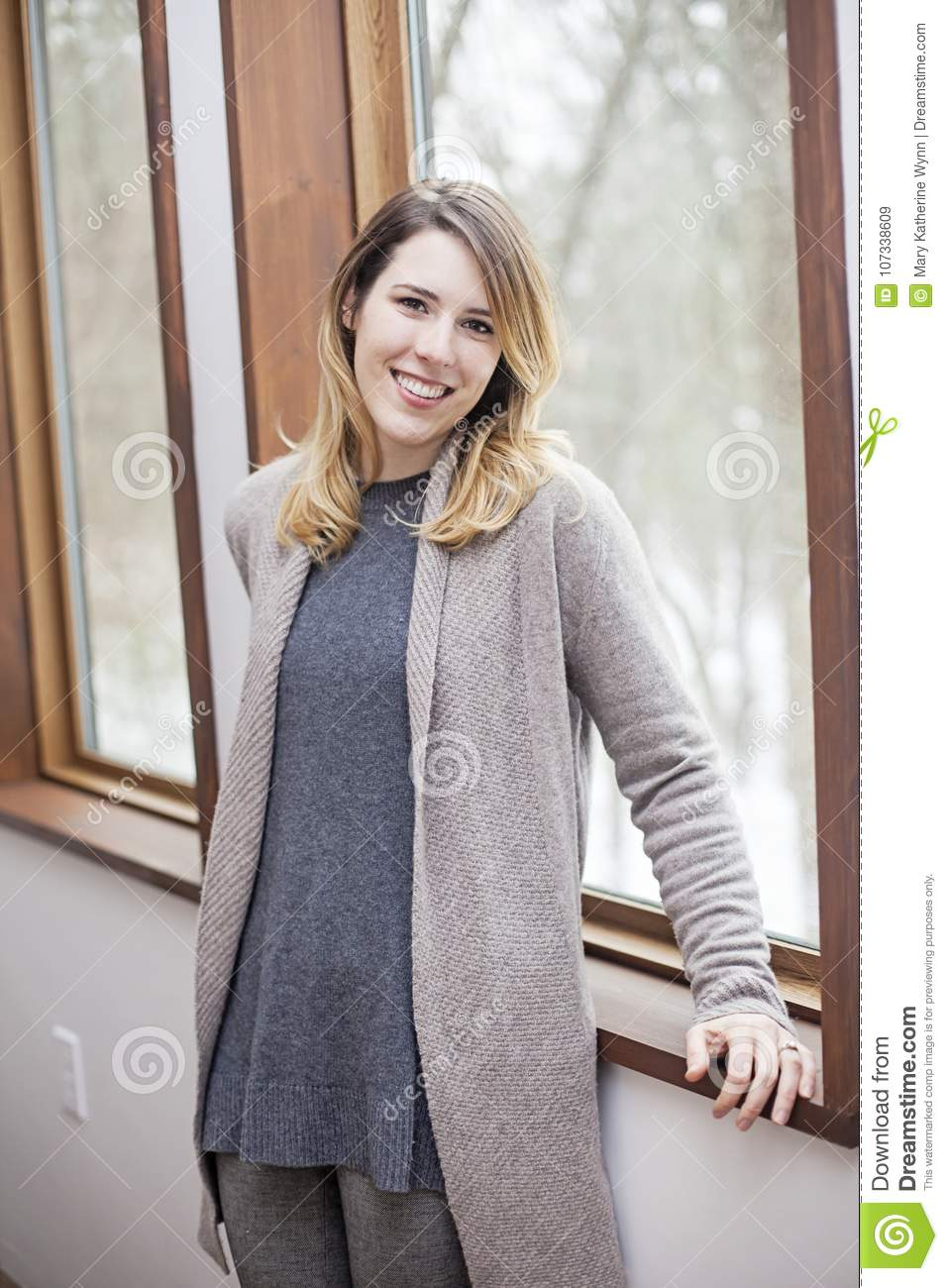 Happy woman at home by window in winter