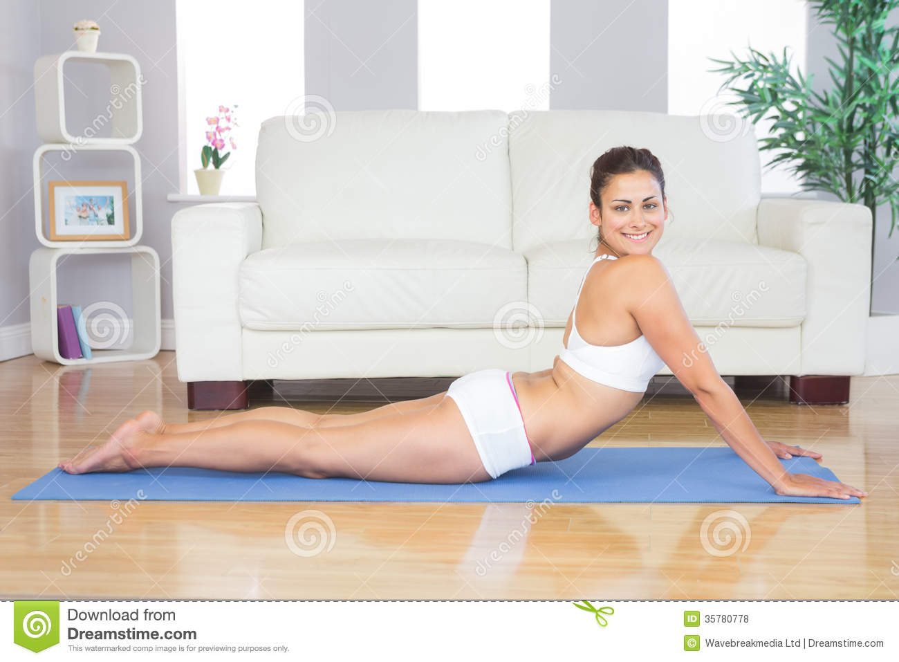 Smiling young woman stretching in a yoga pose on a blue for Living room yoga timetable