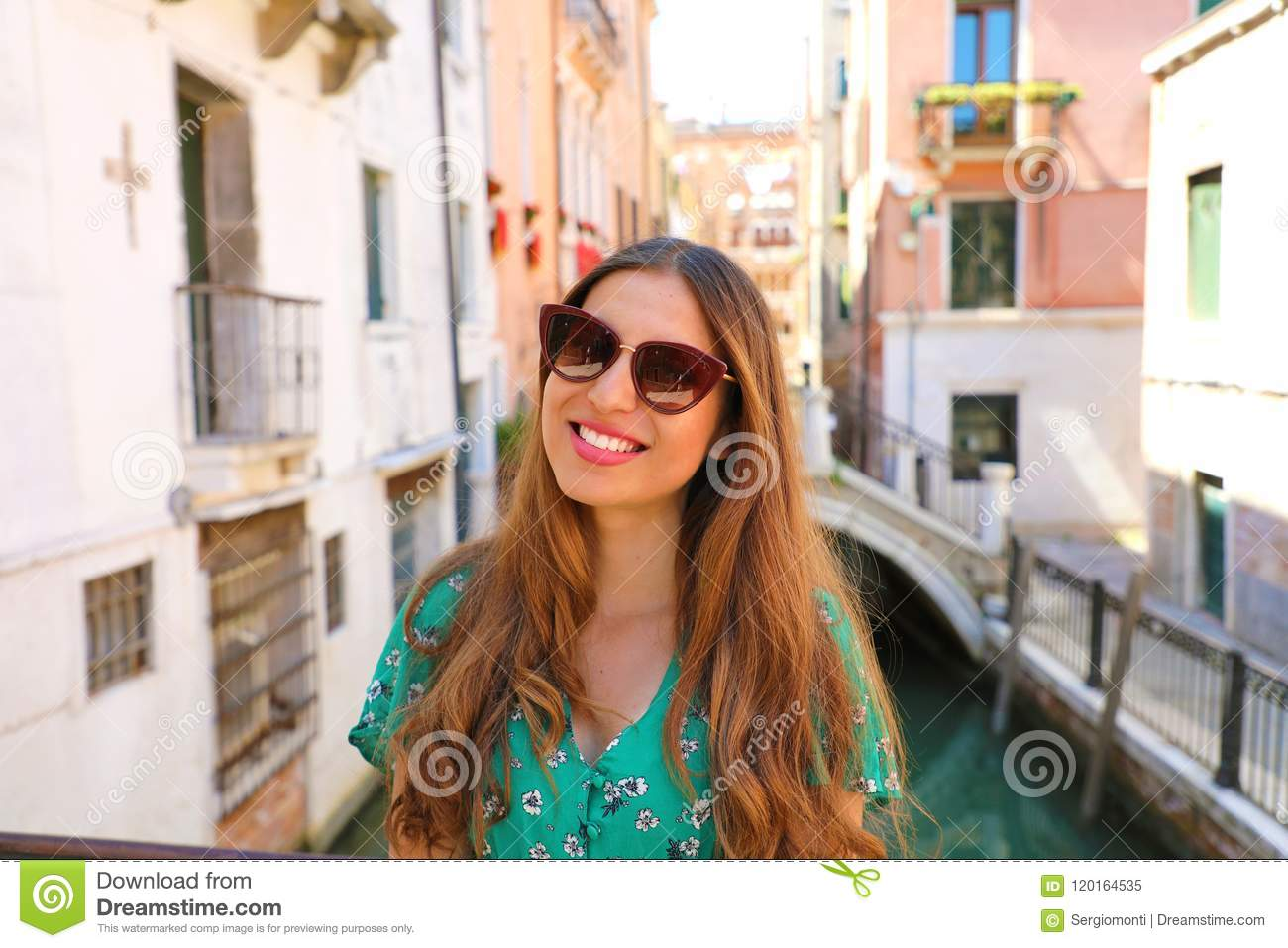 Smiling young woman with sunglasses and green dress in Venice. Happy beautiful girl standing on Venice bridge on canal, Italy