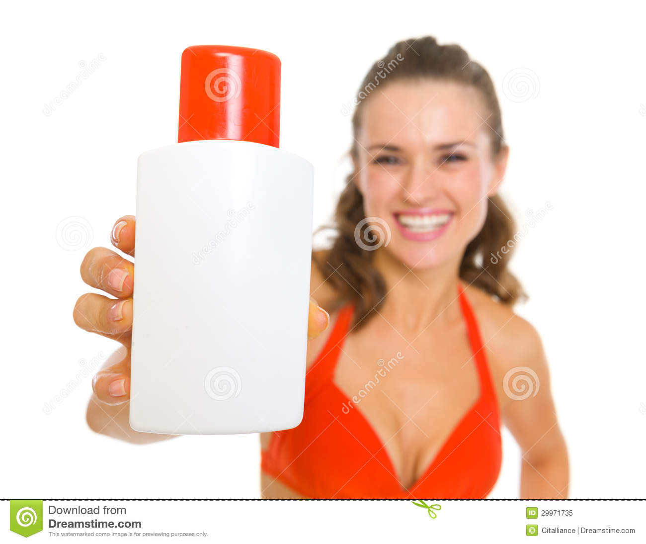 Smiling woman in swimsuit showing sun block creme