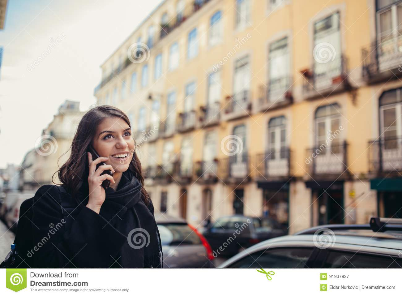 Smiling young woman talking on her smartphone on the street.Communicating with friends,free calls and messages for young people.