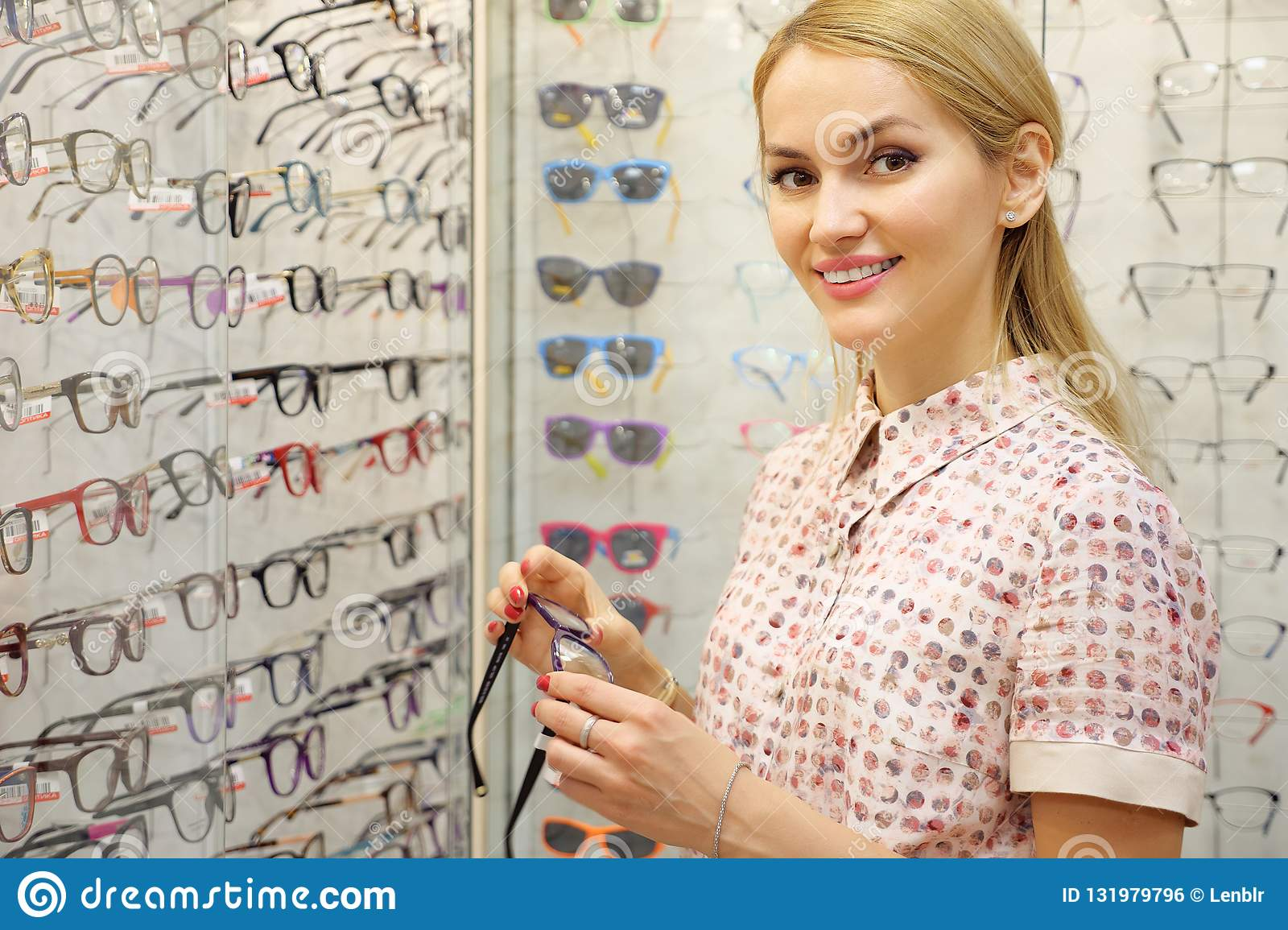Smiling young woman trying new glasses at optician store