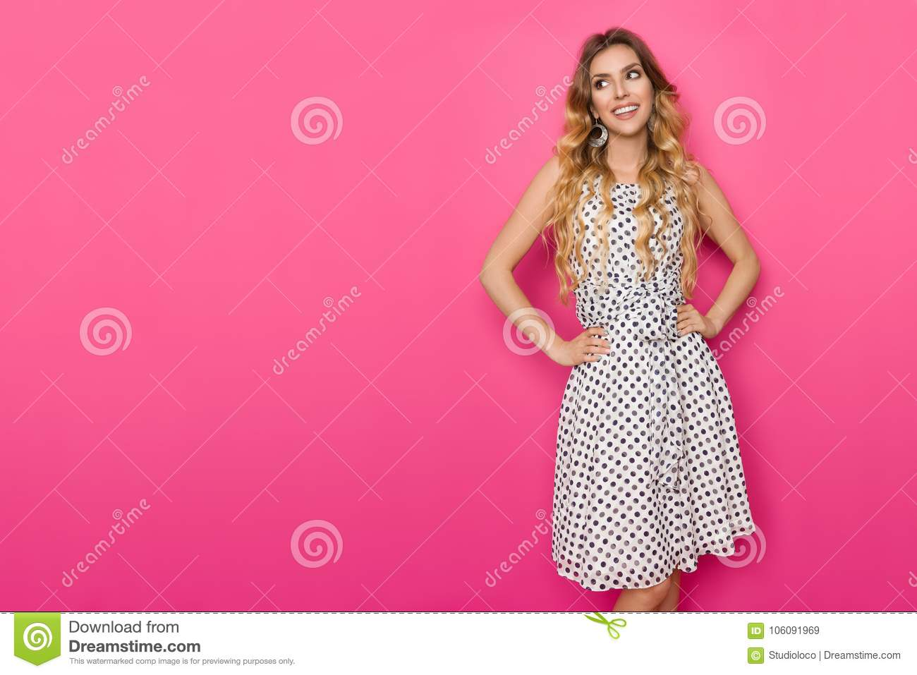 e3621a97bfb8 Beautiful young woman in white dotted summer dress posing with hands on hip