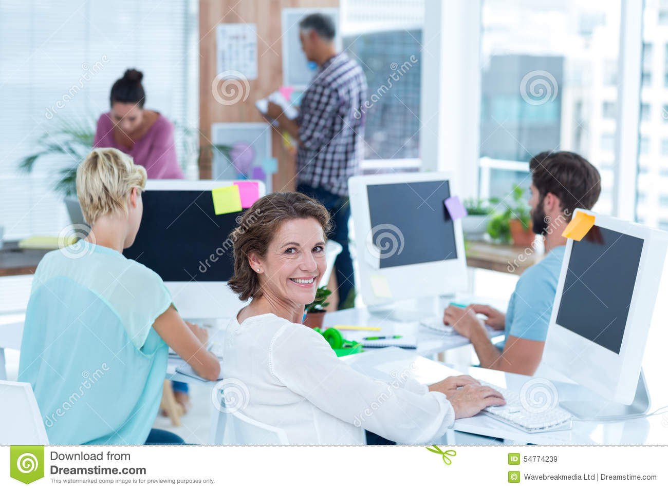 Smiling young woman working with her colleague at desk