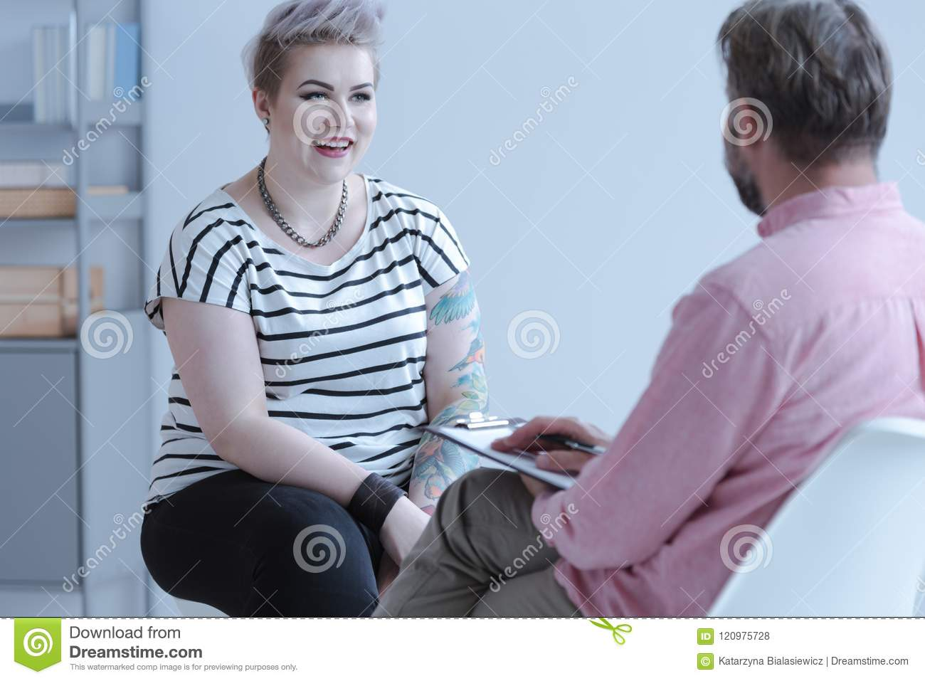 Smiling young woman with tattoos talking to a counselor about bu