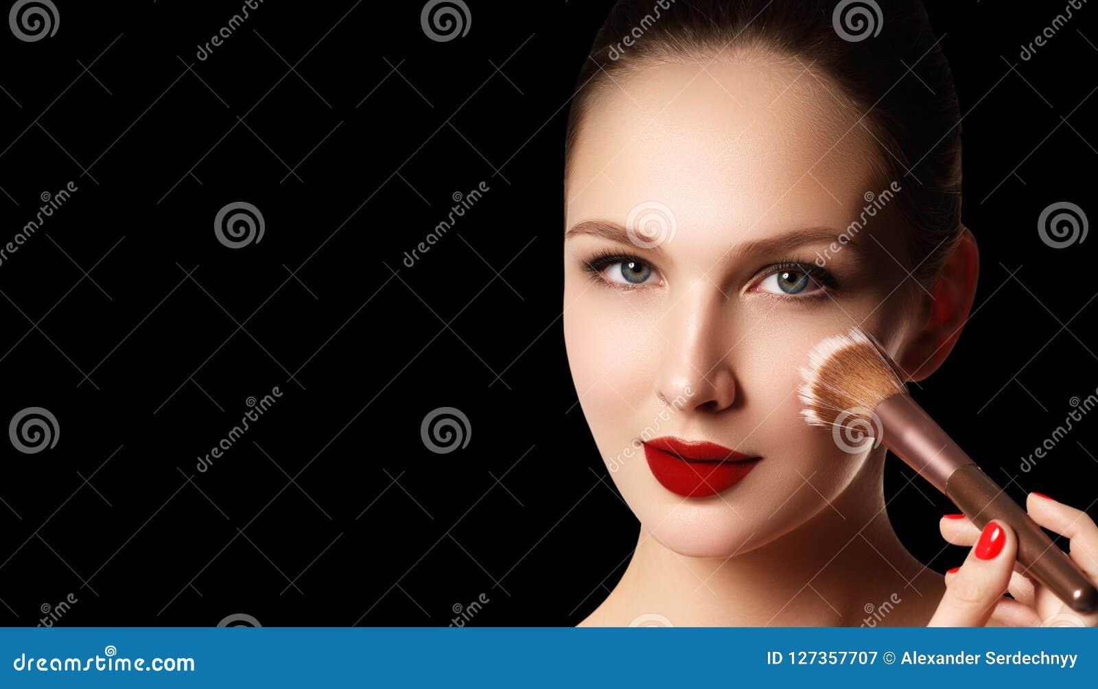 Smink och skönhetsmedel Skönhetkvinnaframsida som isoleras på svart backg