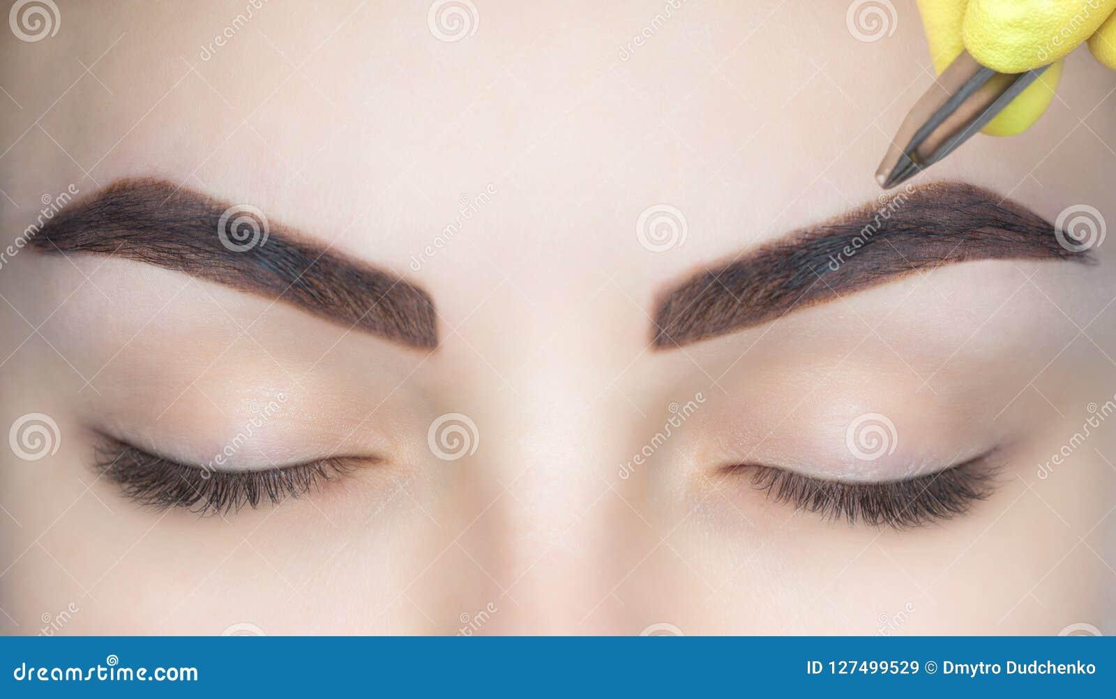 Sminkkonstnären plockar hennes ögonbryn från en ung kvinna i en skönhetsalong