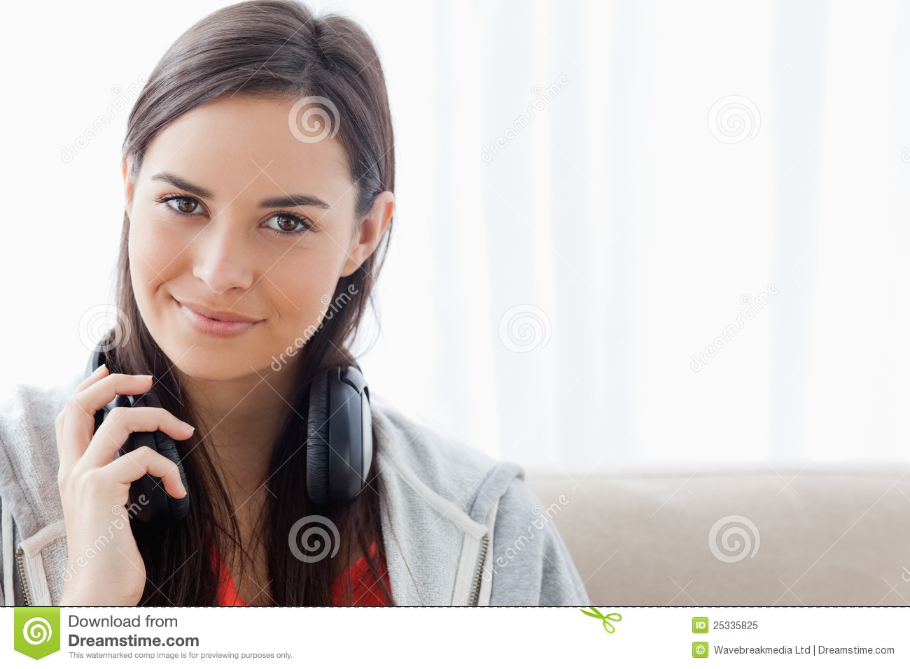 A smirking woman with headphones looks into the camera