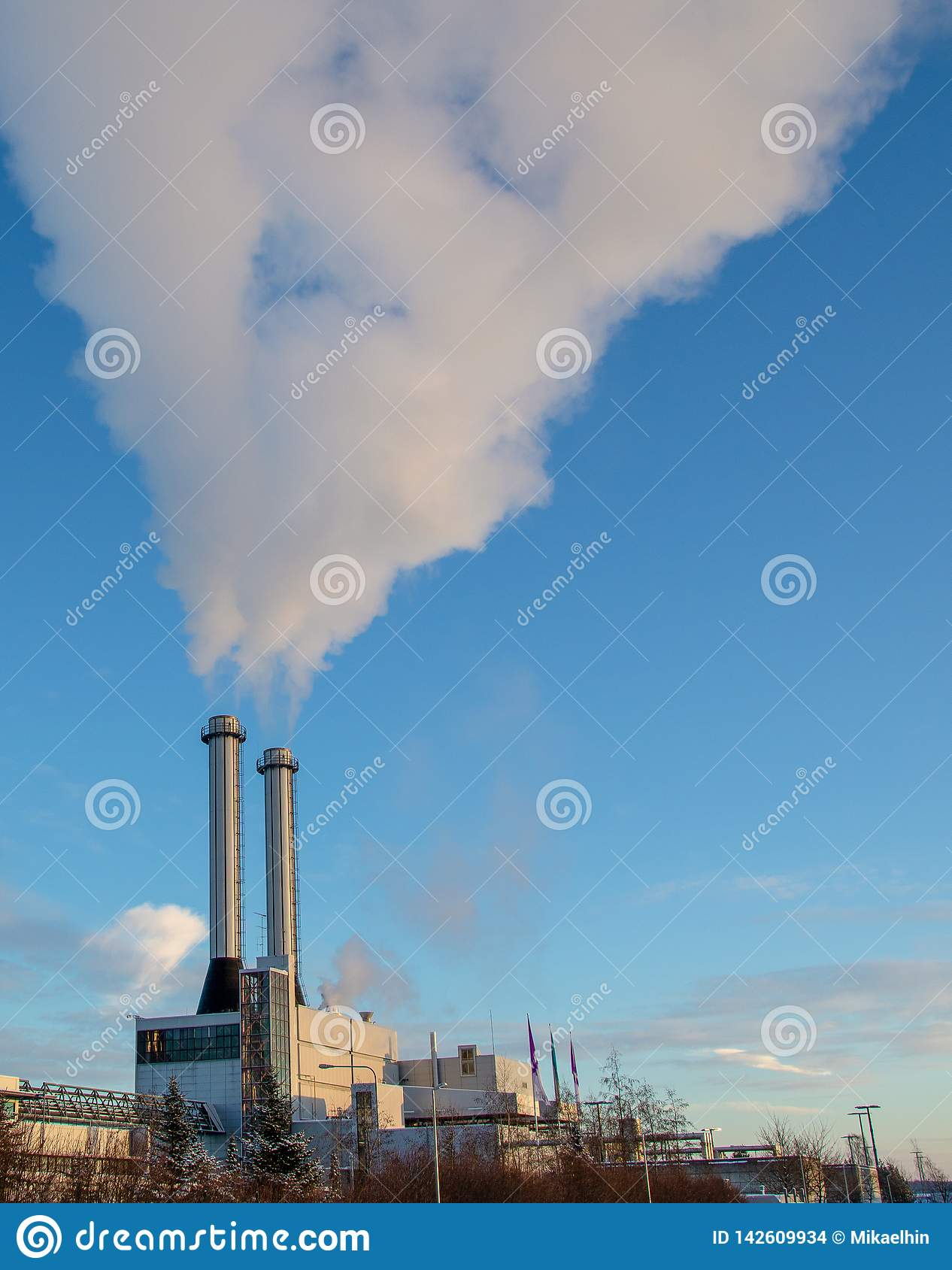 Smoke exiting two chimneys is winter