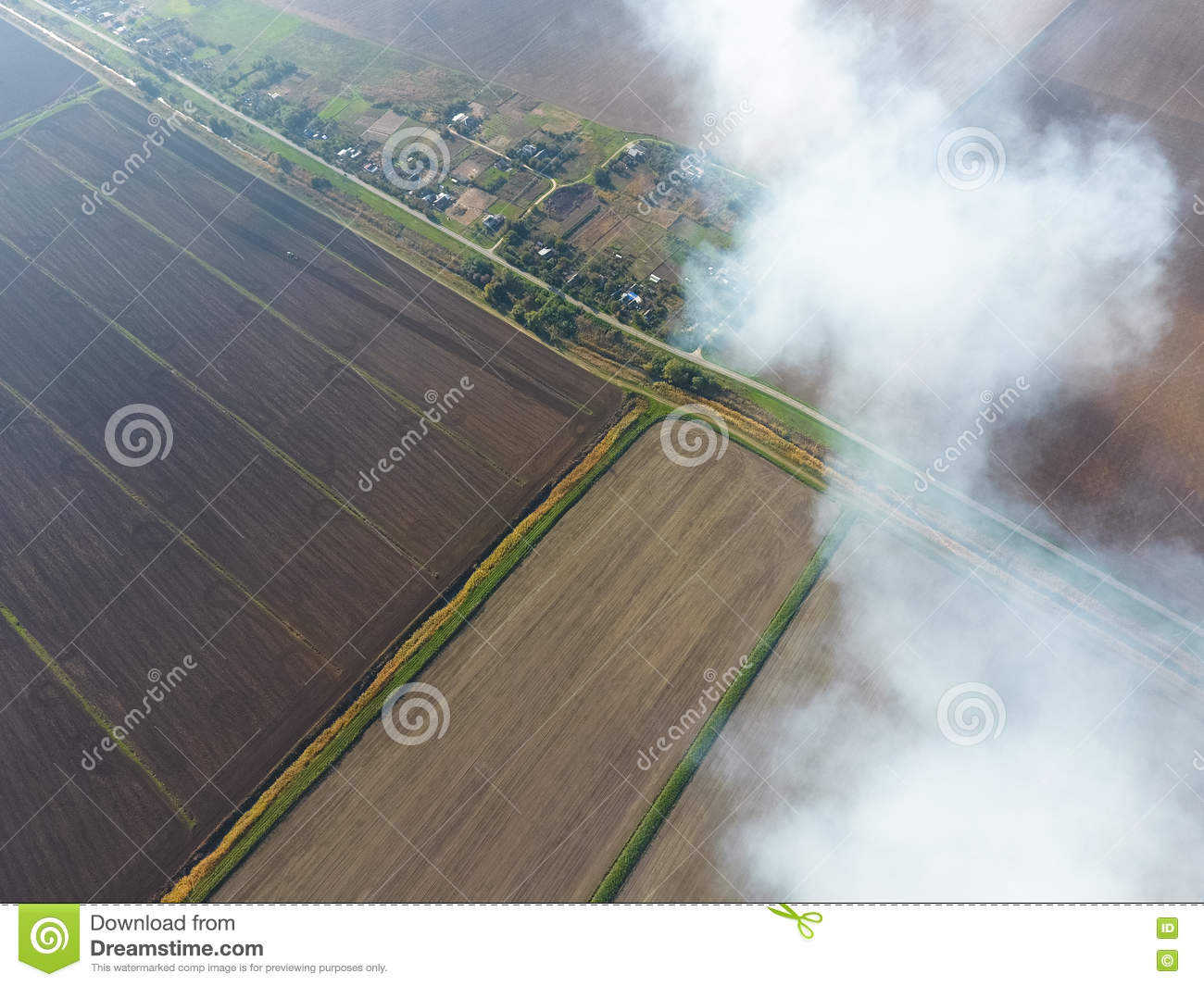 The smoke over the village. Clubs of smoke over the village houses and fields. Aerophotographing areas