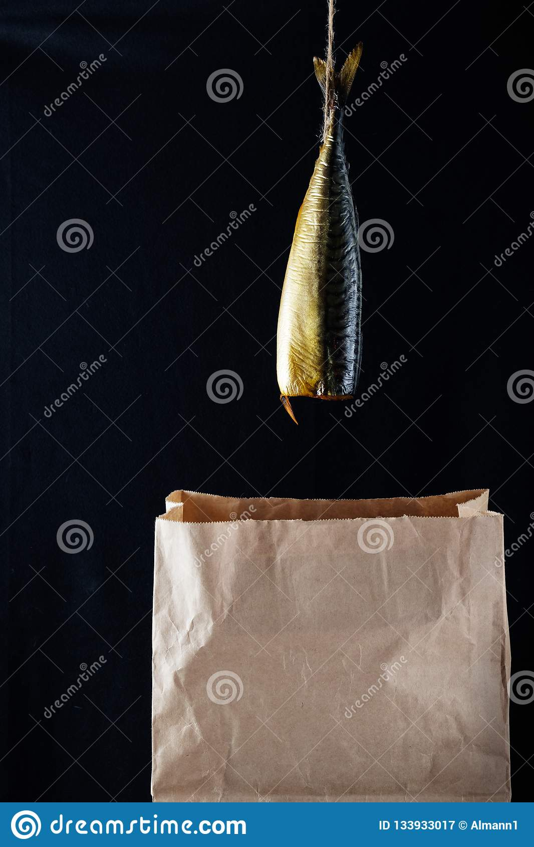 Smoked fish mackerel on the paper bag in the black wooden background