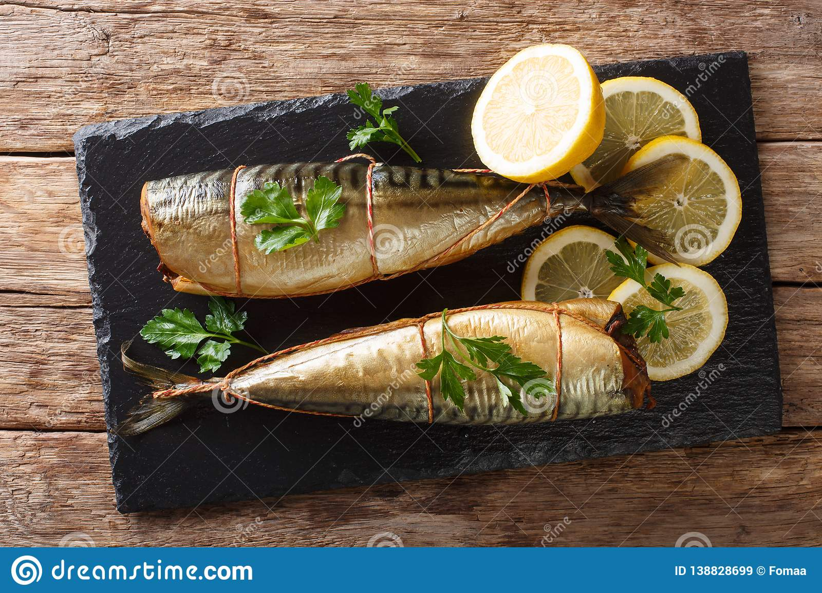 Smoked mackerel with lemons and parsley closeup on a slate board on the table. horizontal top view