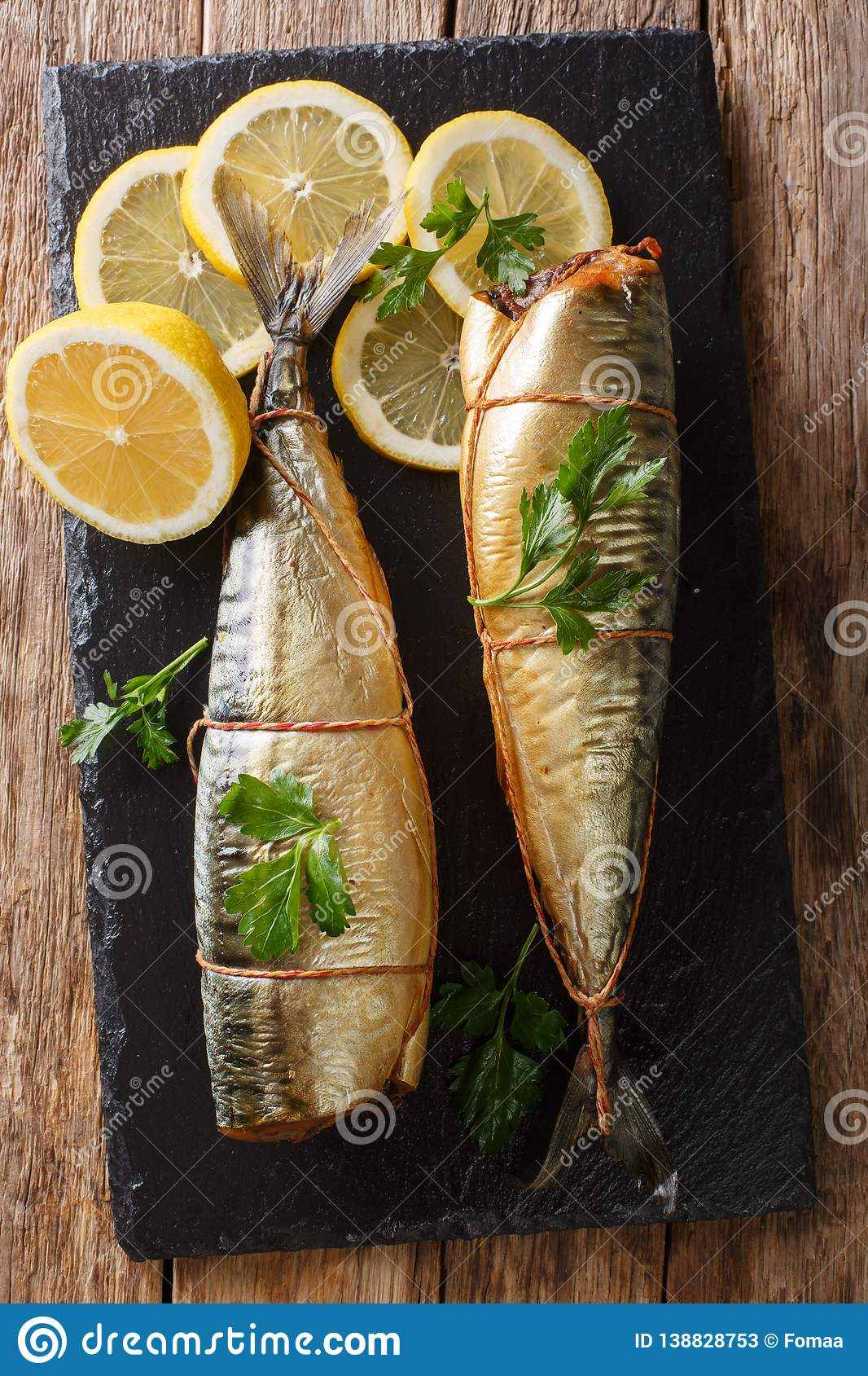 Smoked mackerel with lemons and parsley closeup on a slate board on the table. Vertical top view