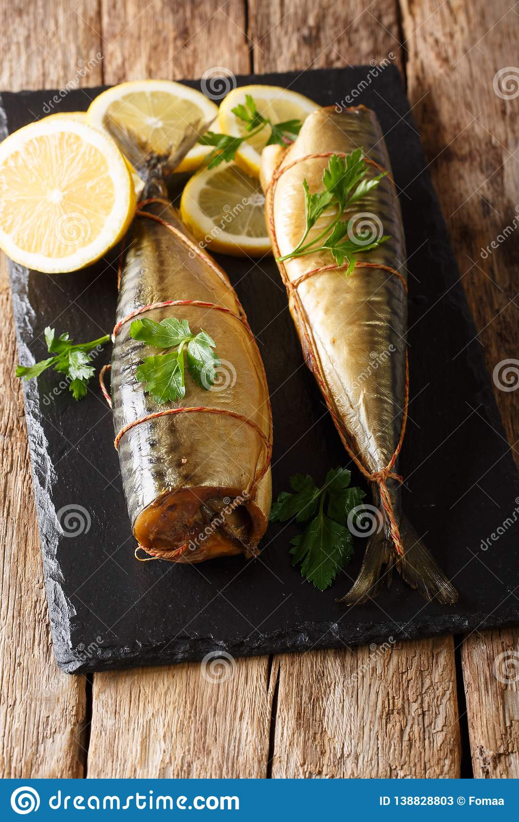 Smoked mackerel snack food served with lemons and parsley closeup on a black stone board. vertical