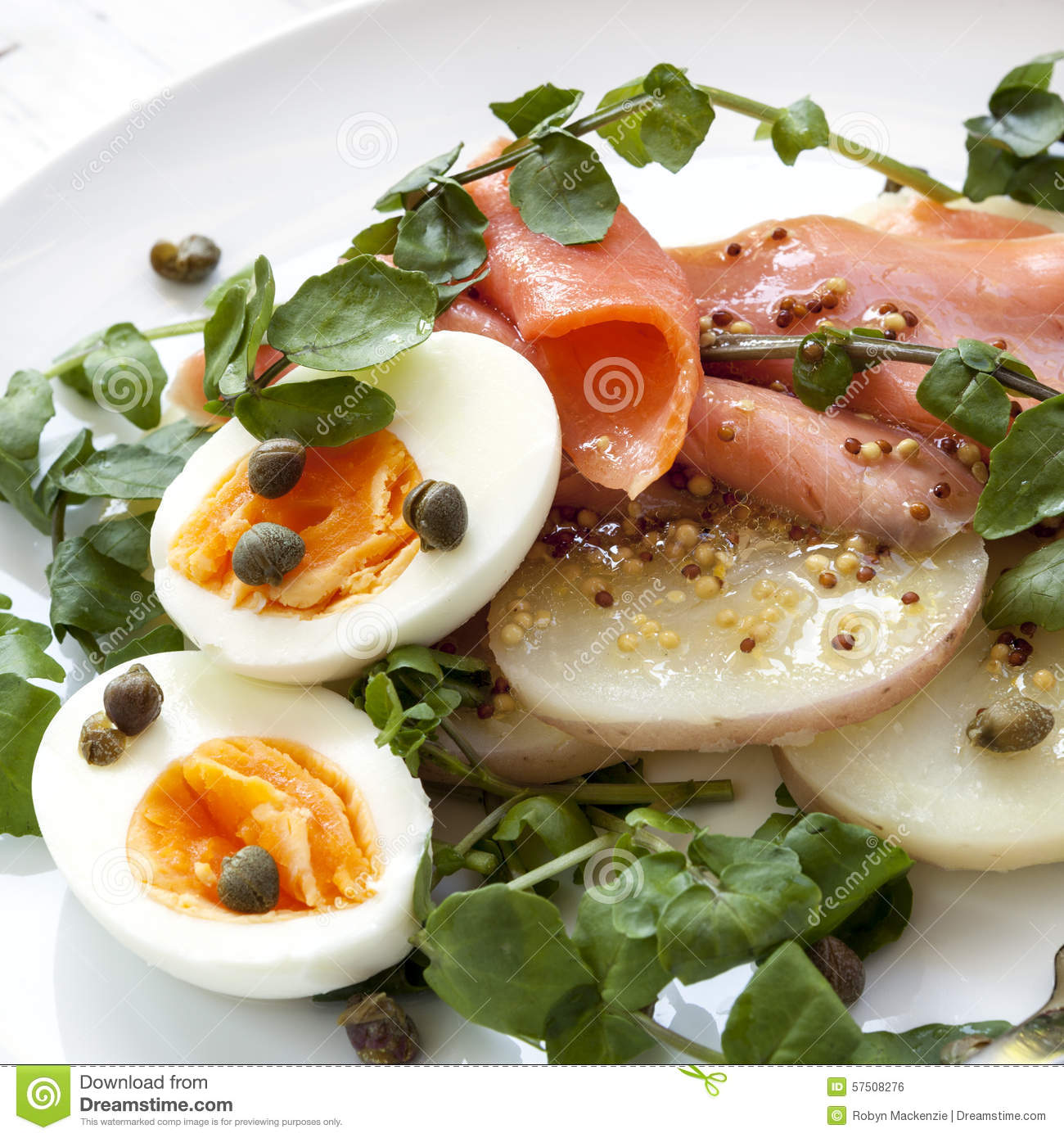 Smoked salmon, potato and egg salad, garnished with watercress, capers ...