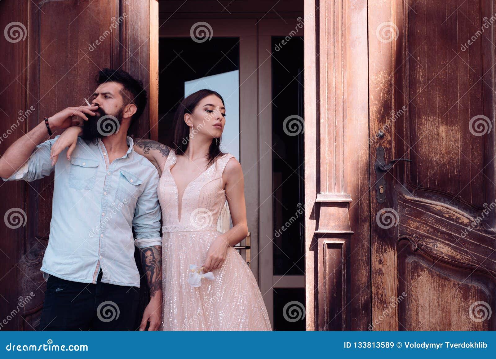 Smoking addiction. Couple in love have smoking break. Romantic couple of sensual woman and bearded man smoke outdoor