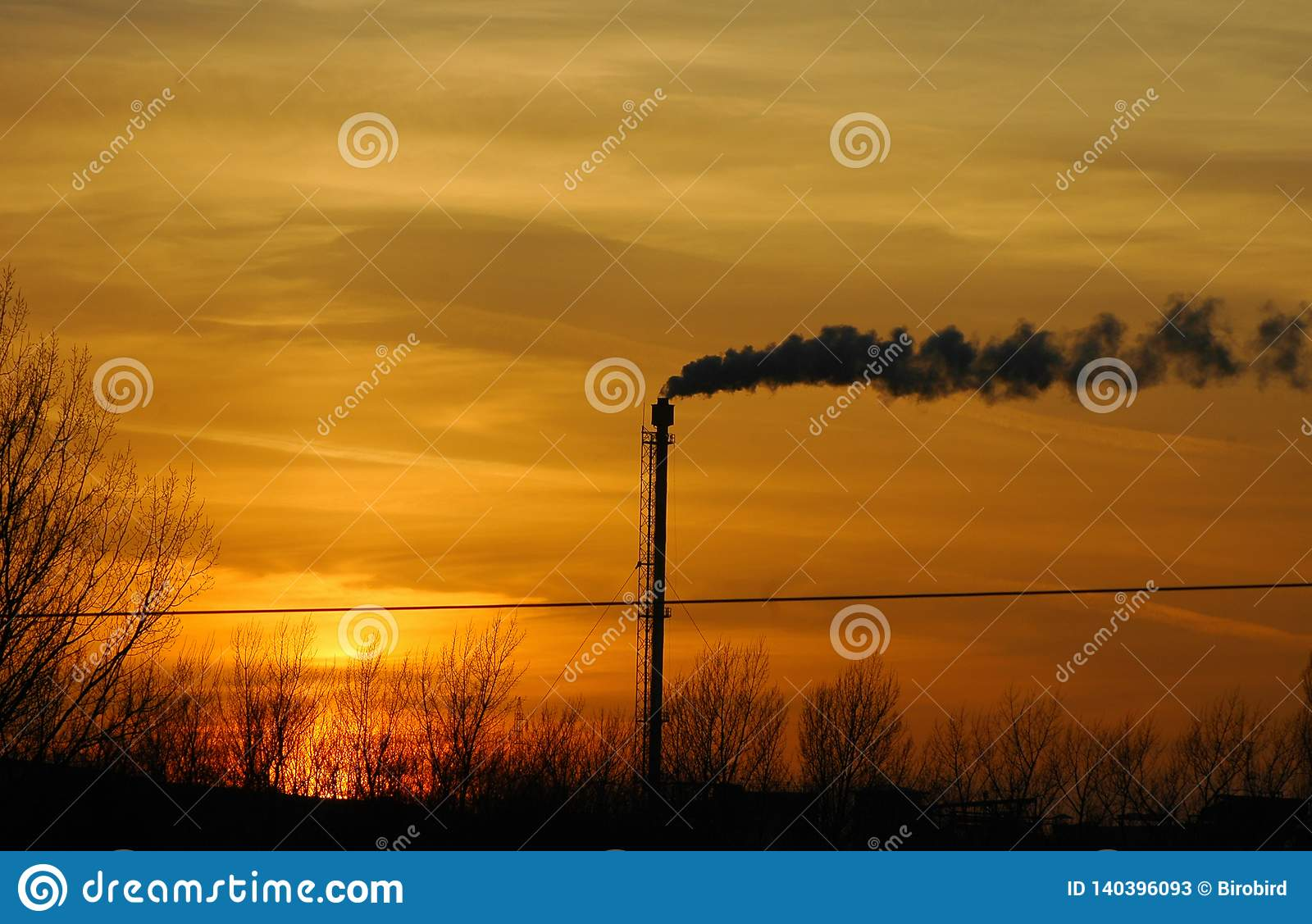 Smoking chimney of a factory in the sunset