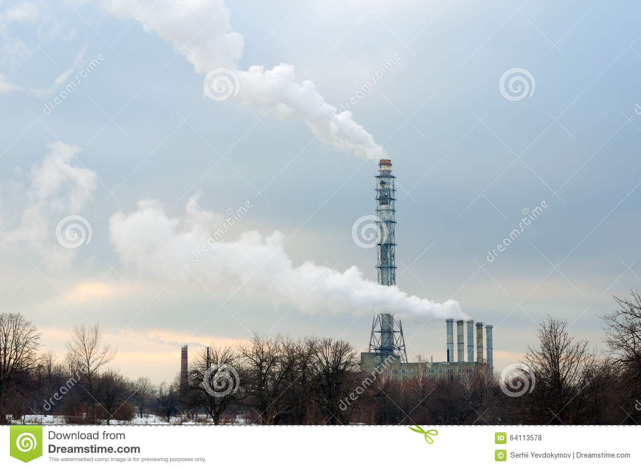 Smoking chimneys boiler on a background of trees, snow and sunset sky