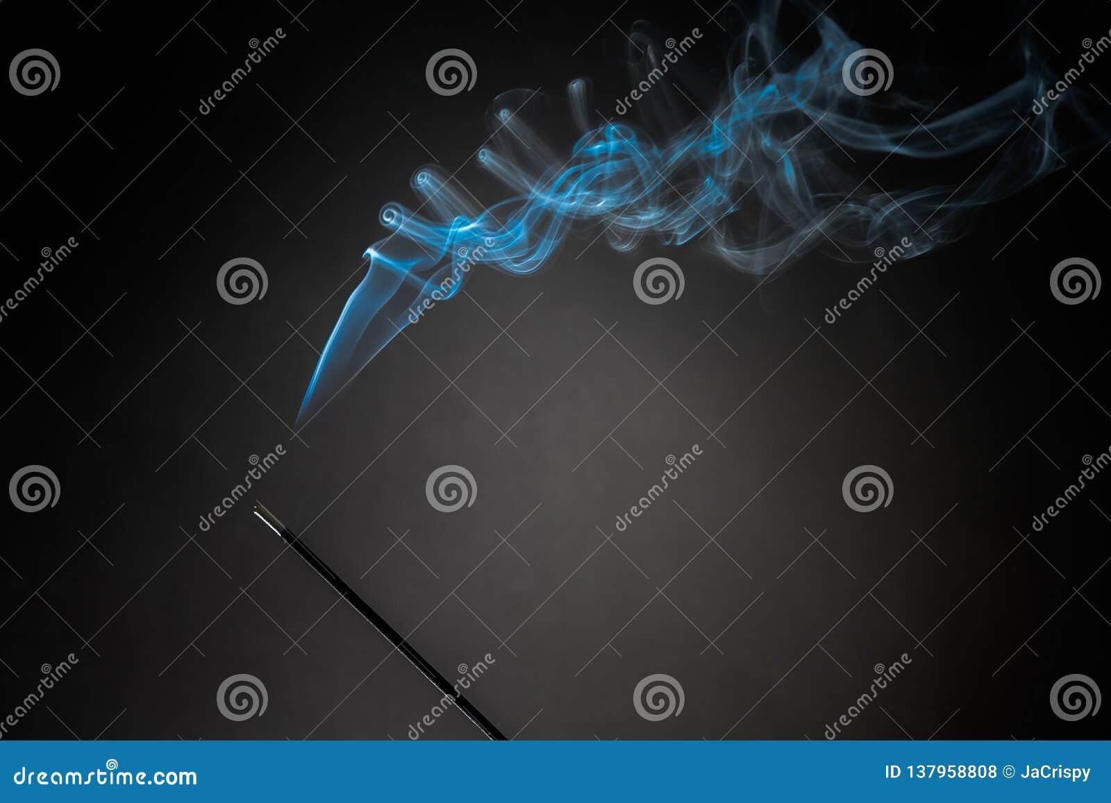 Smoking Incense Stick With Smoke Going Up On Black