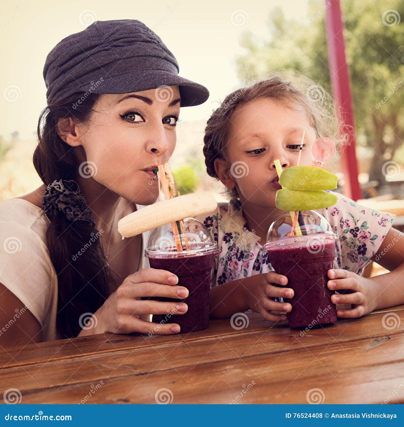 Smoot ягод счастливой девушки ребенк и смешной эмоциональной матери выпивая
