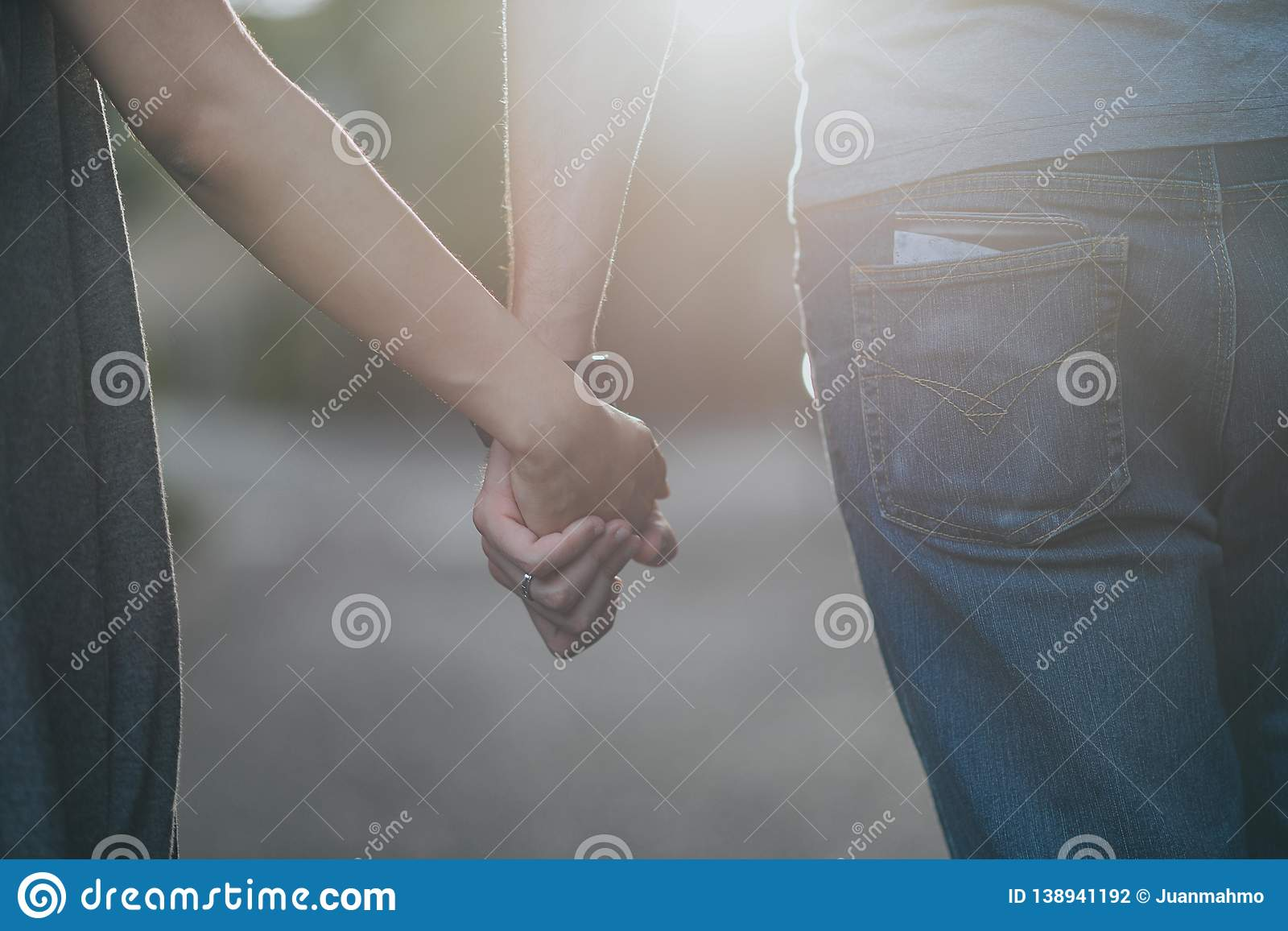 Smooth Focus,Valentine couples walking hand in hand, along the road with white light coming straight from the front and promised