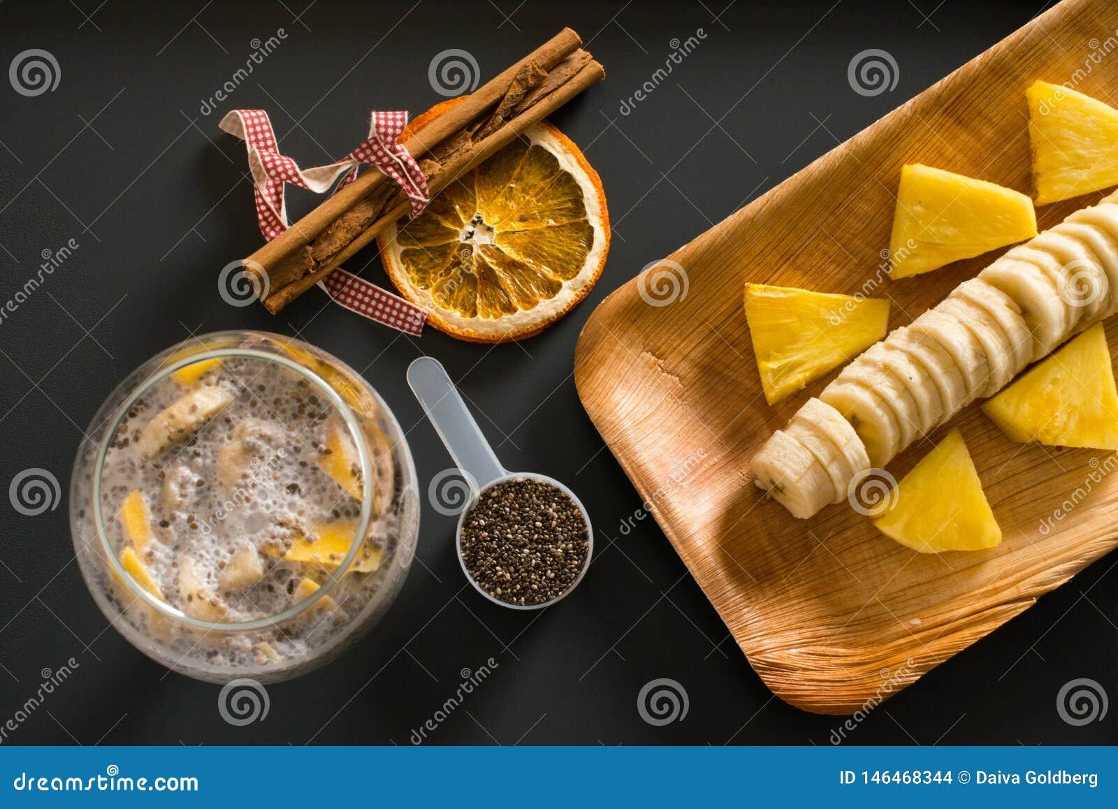 Smoothie манго с бананом, семенами chia и молоком кокоса на темной предпосылке
