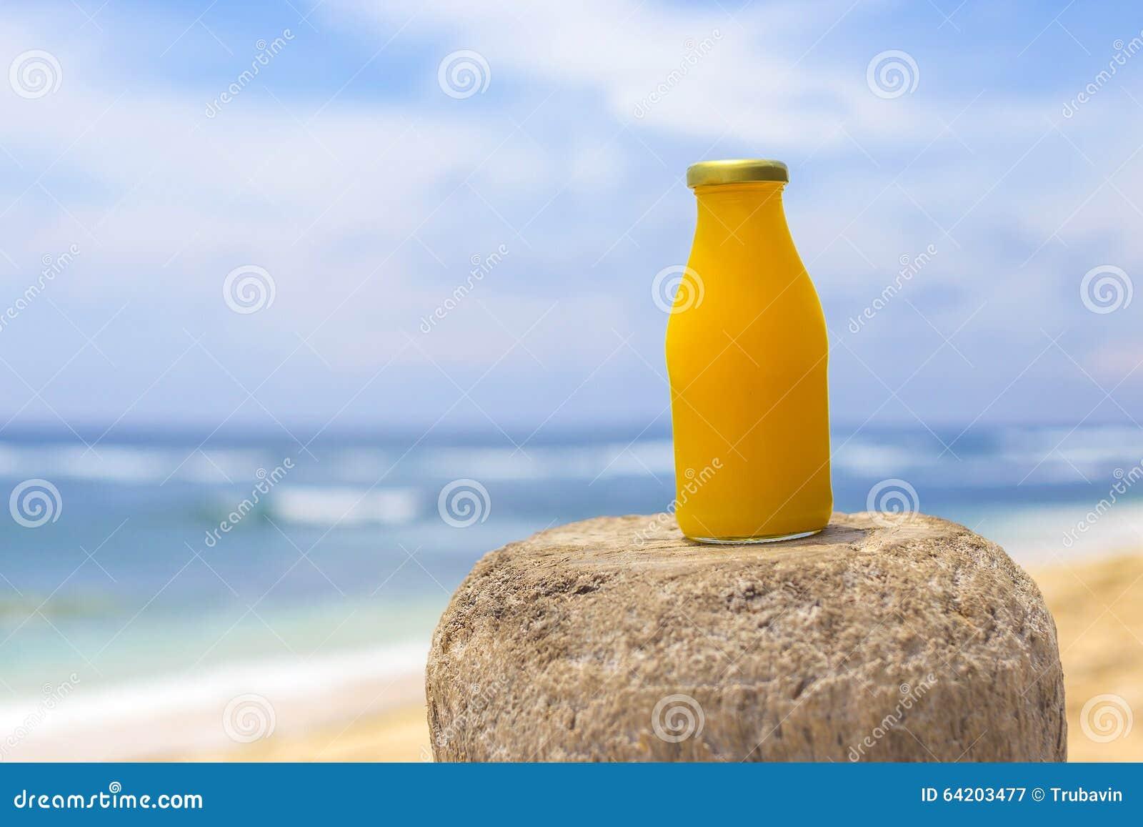 Smoothie anaranjado sano con la playa