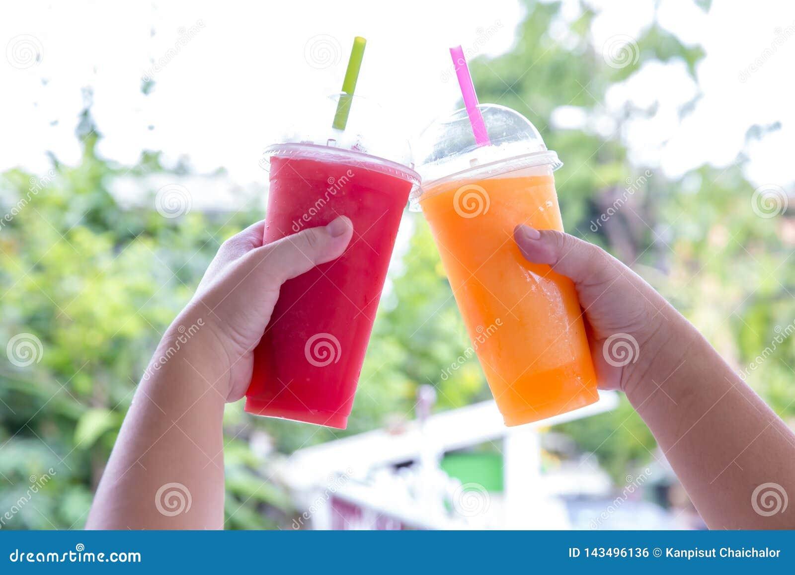 Smoothie de la fruta Mano que sostiene la taza pl?stica de smoothie colorido de la fruta en el caf? lindo Mano que sostiene la ta