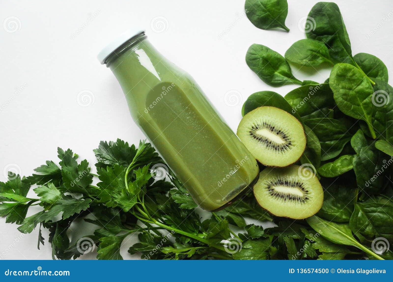 Smoothie o jugo verde en tarros e ingredientes en el fondo blanco Adiete el concepto Detox Comida estupenda