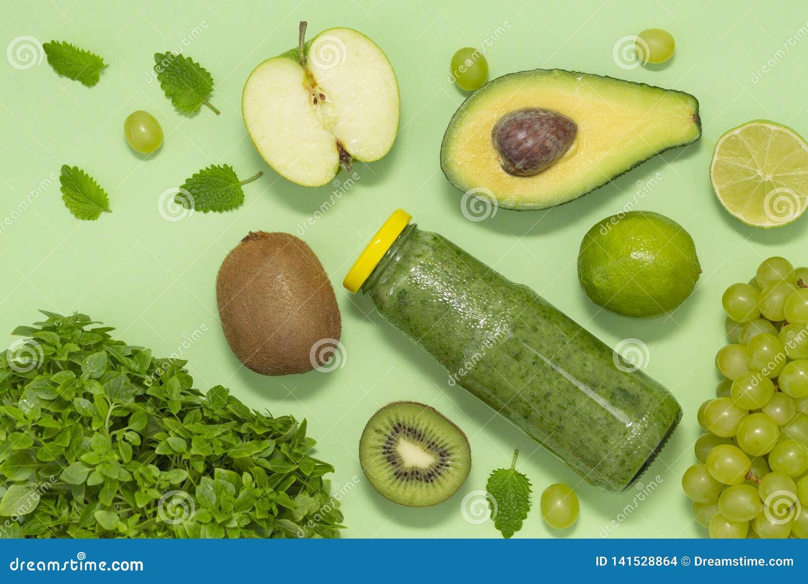 Smoothie verde colorido en botella en el fondo verde, visión superior