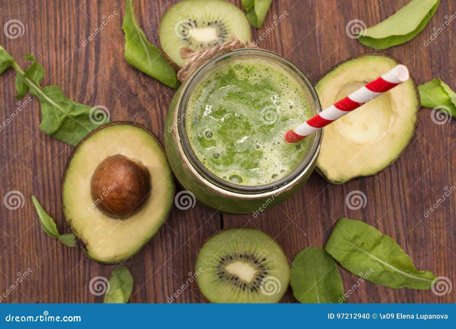 Smoothie vert sain avec la banane, les épinards, l avocat et le kiwi dans bouteilles en verre sur un rustique
