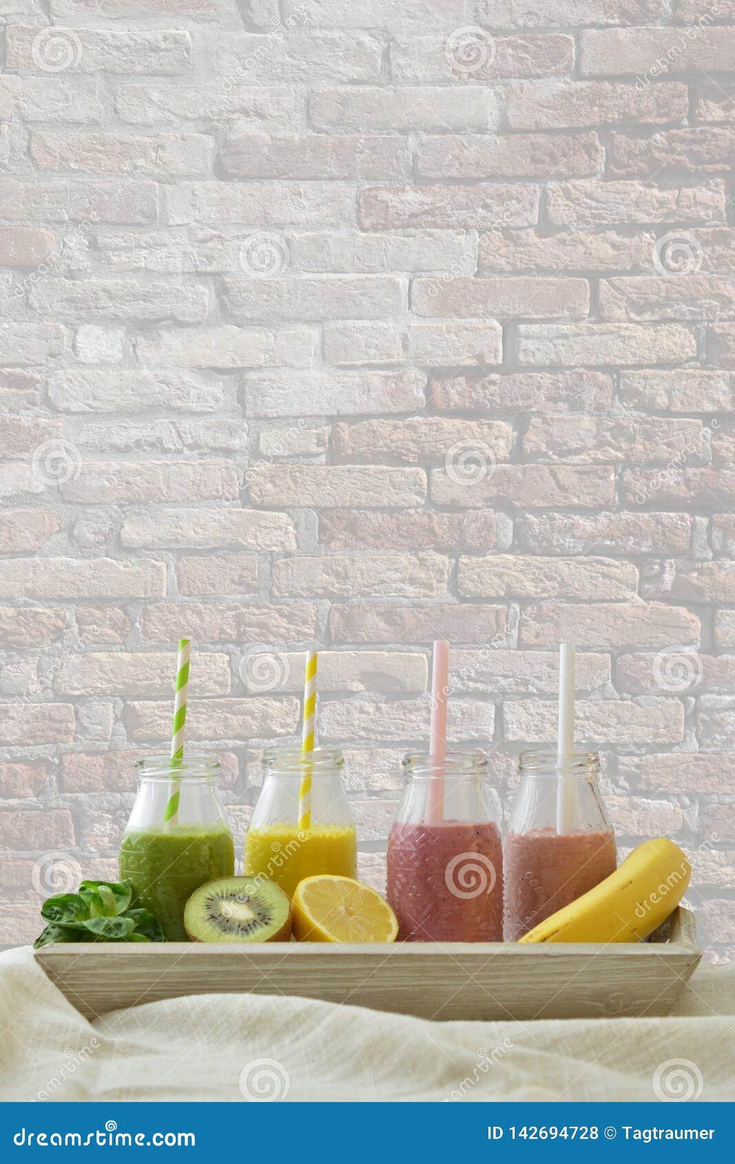 Smoothies coloridos de la fruta en fila con las frutas frescas delante de la pared de ladrillo