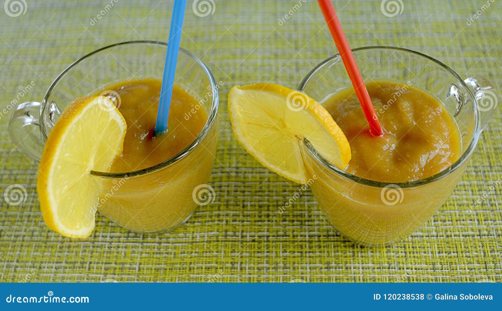 Smoothies fruités avec le citron dans deux stylos en verre avec des pailles