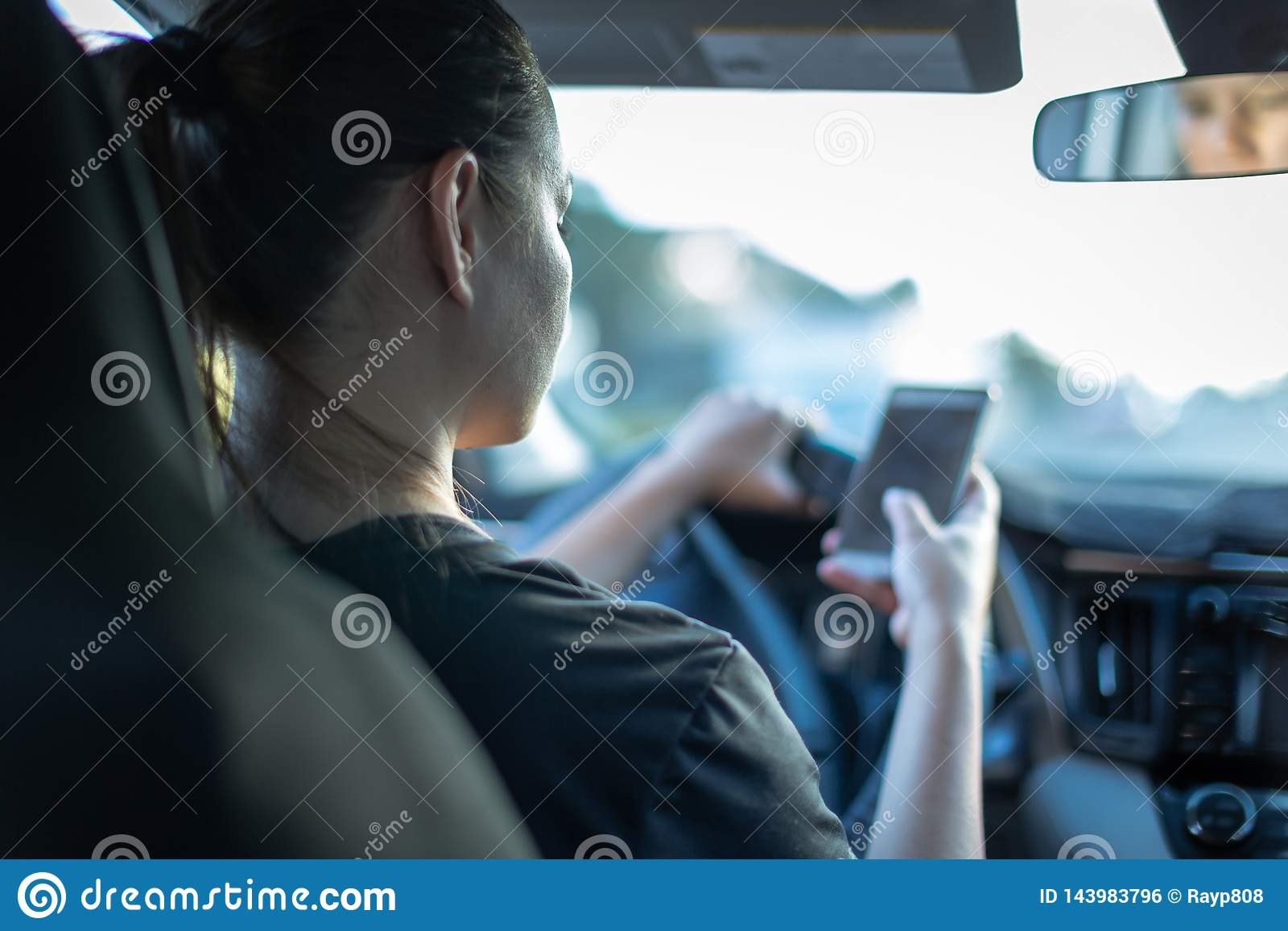 Smsa och körning Kvinna som använder telefonen bak hjulet