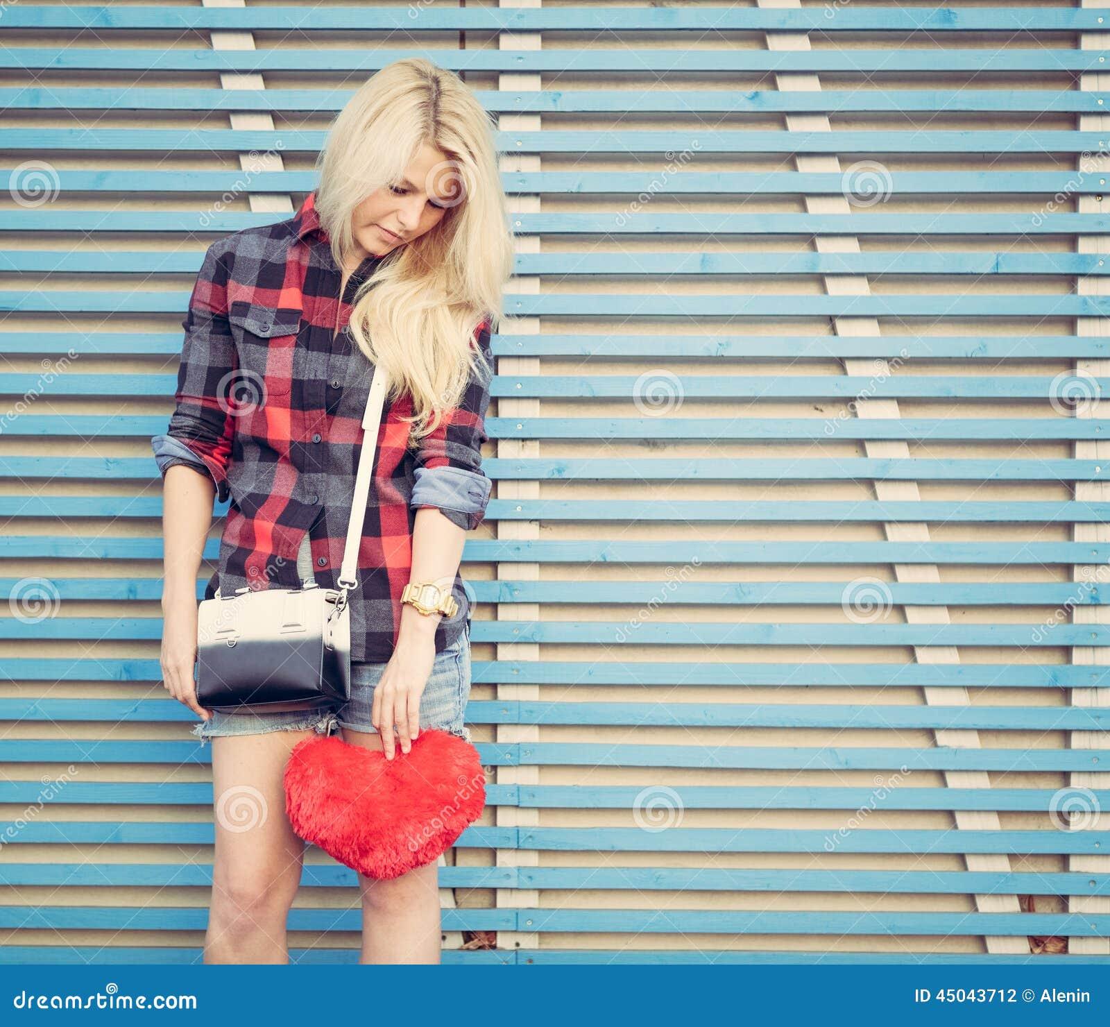 Smutna dziewczyna trzyma czerwonego serce i stojaki blisko ściany barwione drewniane deski