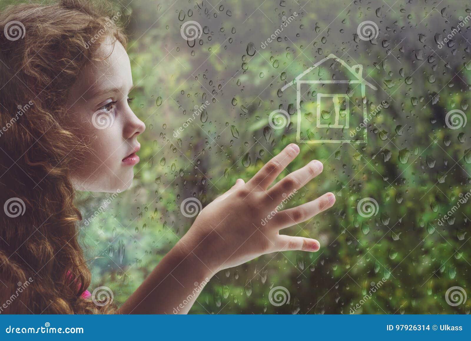 Smutna kędzierzawa mała dziewczynka przyglądająca out podeszczowy opadowy okno