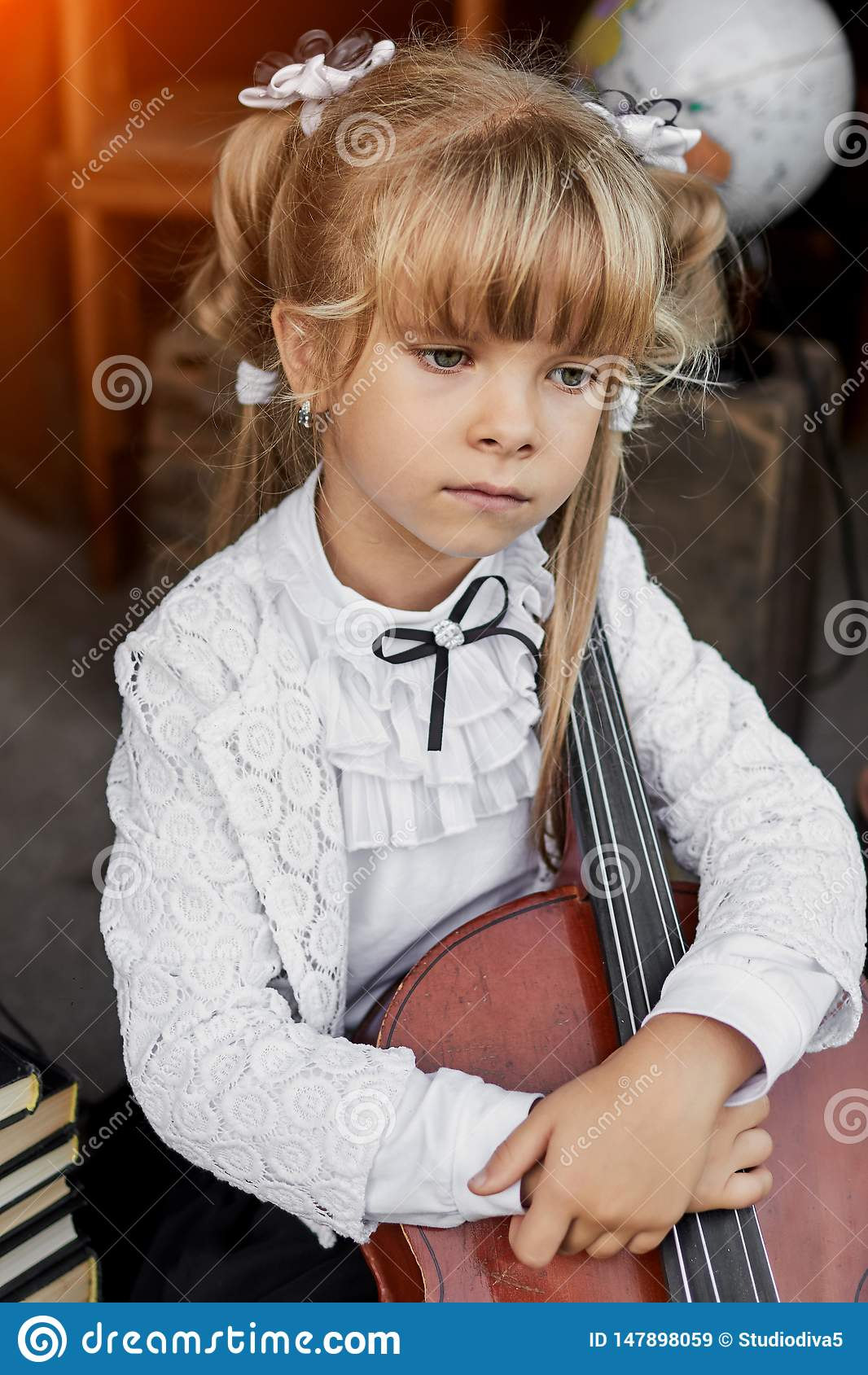Smutna mała dziewczynka trzyma wiolonczelę