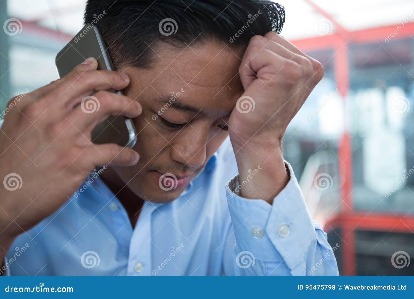 Smutny biznesmen opowiada na telefonie komórkowym