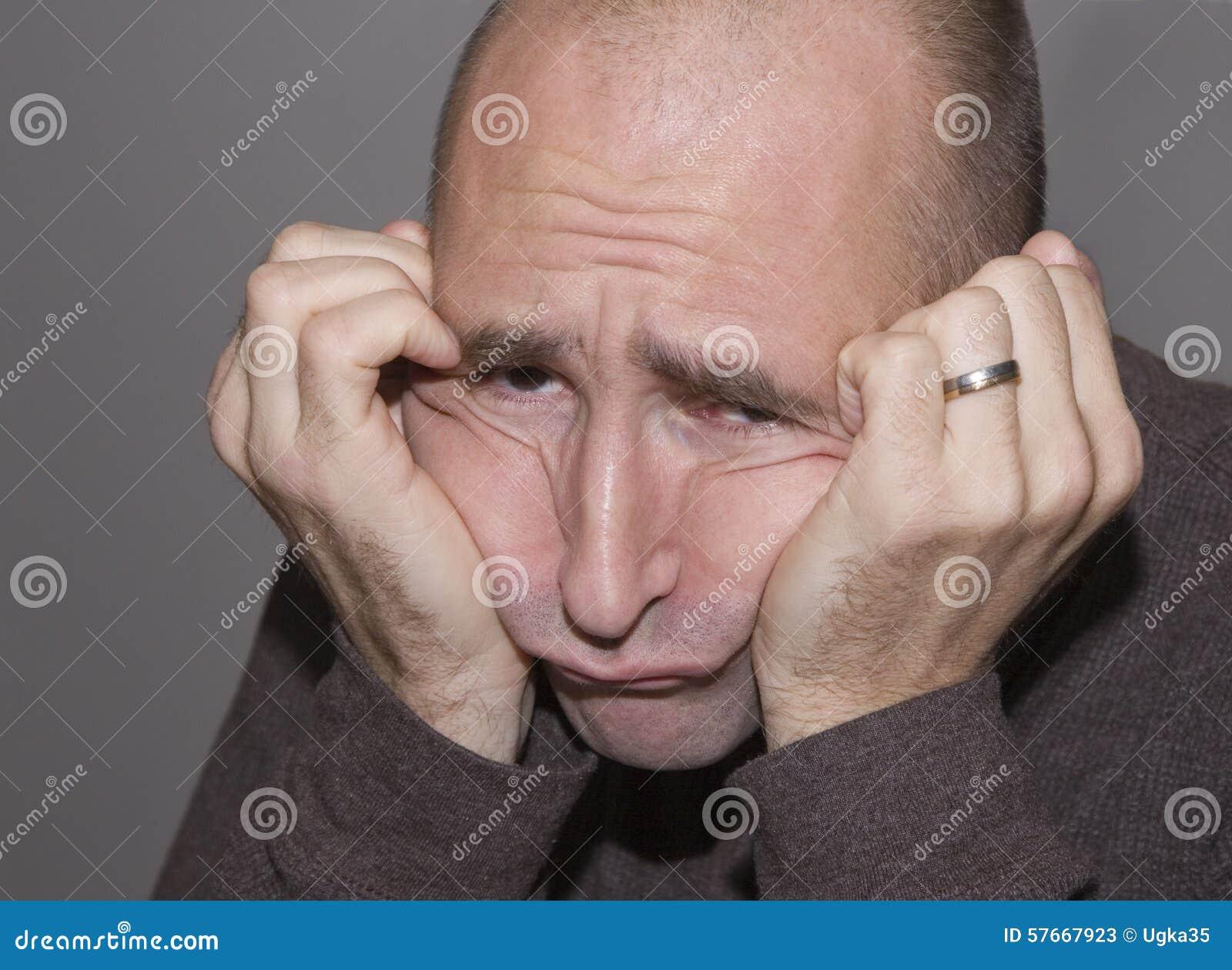 Smutny lub sfrustowany mężczyzna odpoczywa jego głowę w jego ręki