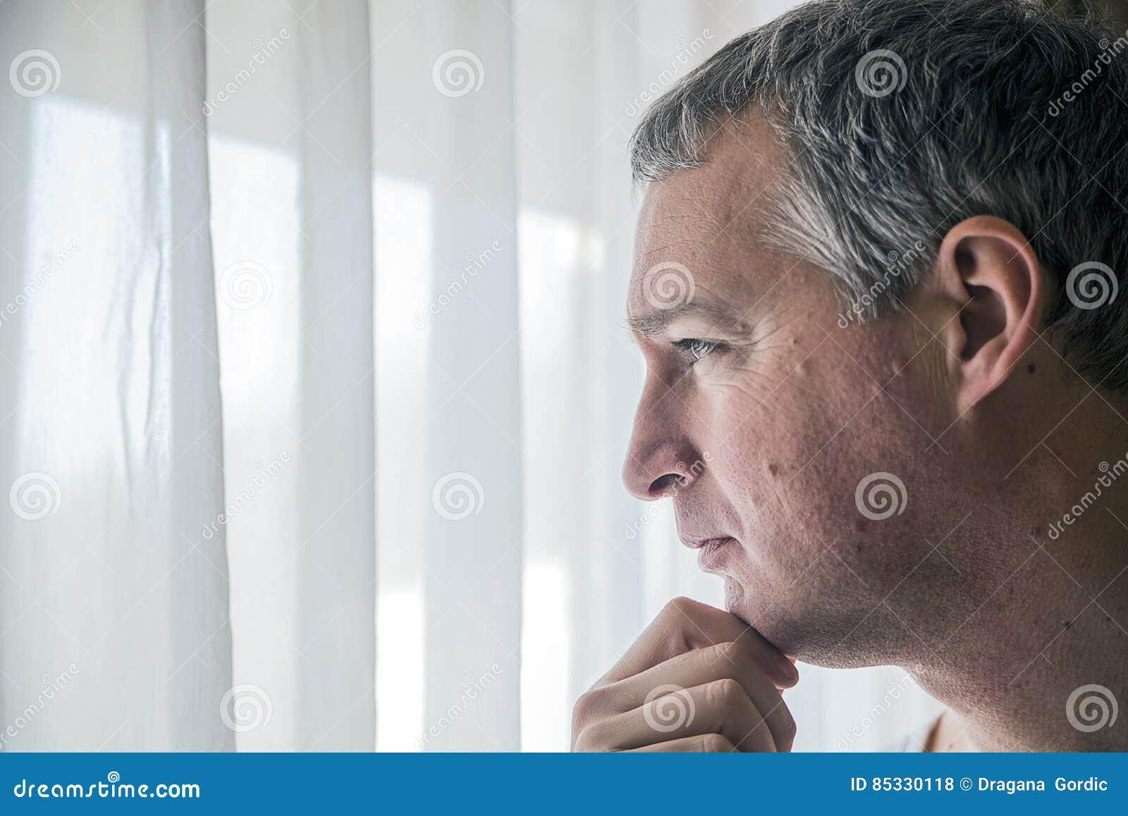 Smutny mężczyzna przyglądający out okno Czuciowy beznadziejny Przygnębiony dorośleć mężczyzna pozycję blisko okno