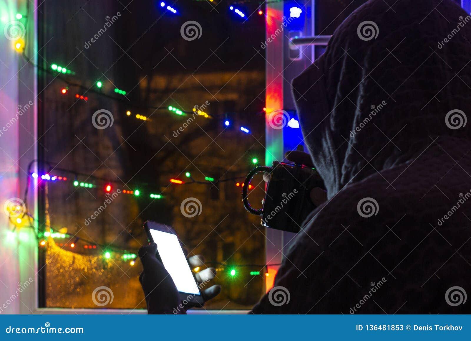 Smutny mężczyzna w kapiszonie z smartphone w zamazanym bokeh na tle okno dekorujący z girlandami z pustym,