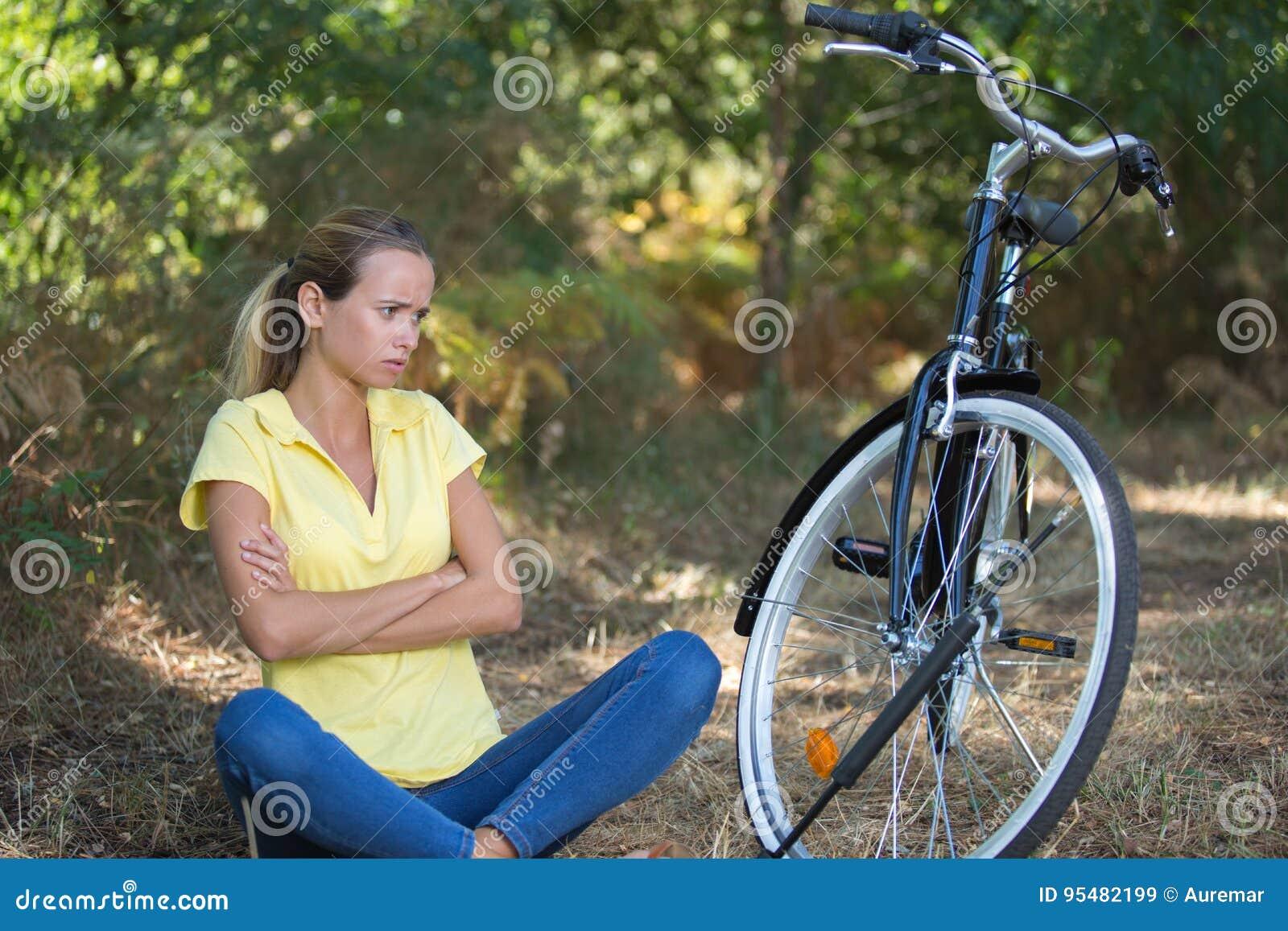 Smutny młodej kobiety obsiadanie przy parkiem obok bicyklu