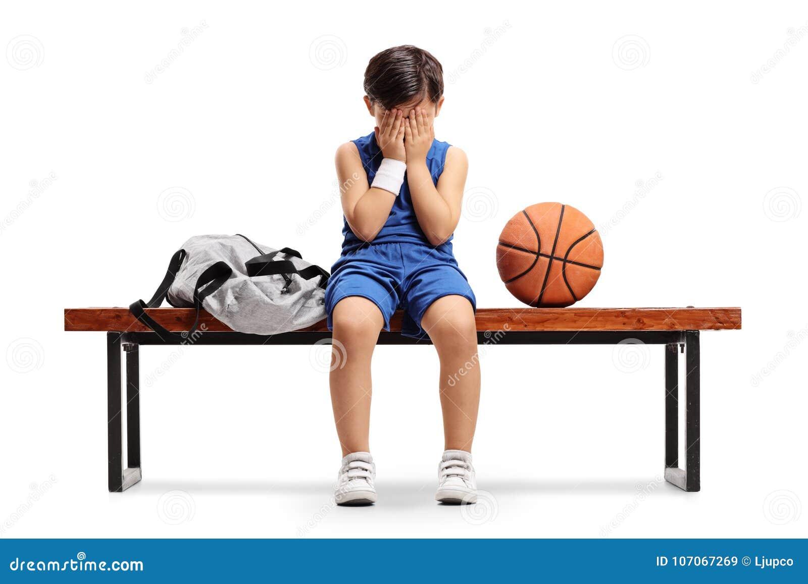 Smutny mały gracza koszykówki obsiadanie na ławce