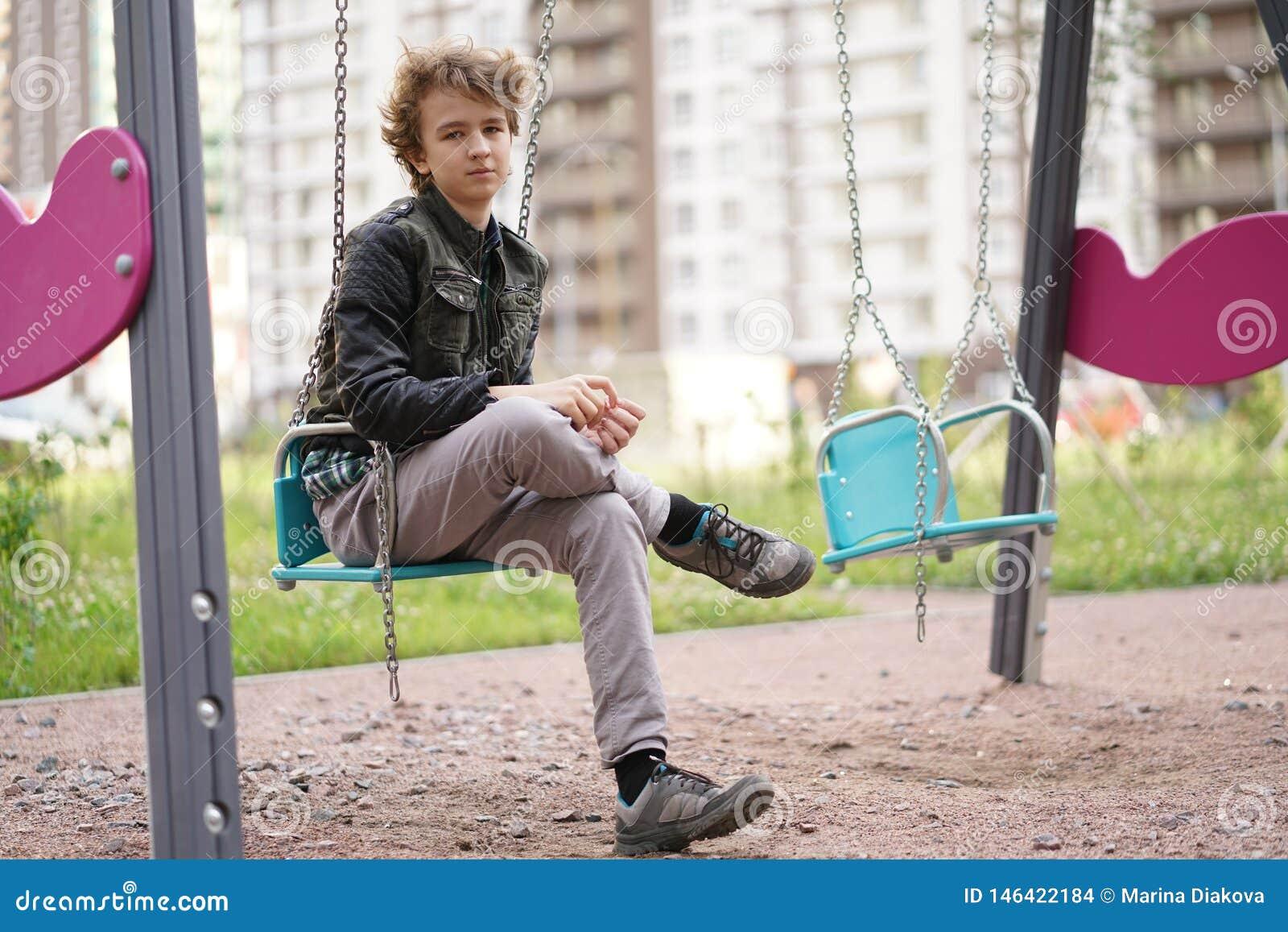 Smutny osamotniony nastolatek plenerowy na boisku szykany adolescencja w komunikacyjnym poj?ciu