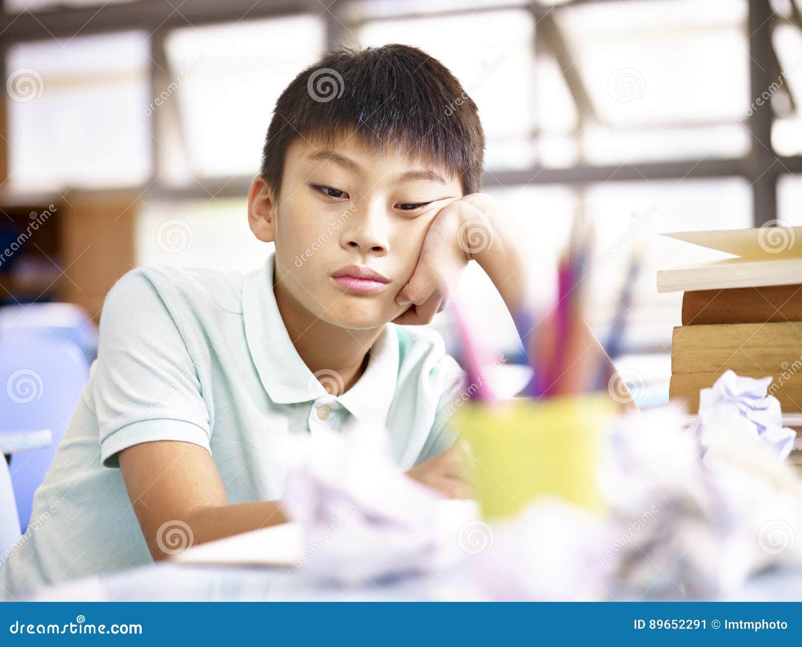 Smutny uczeń siedzi samotnie w sala lekcyjnej