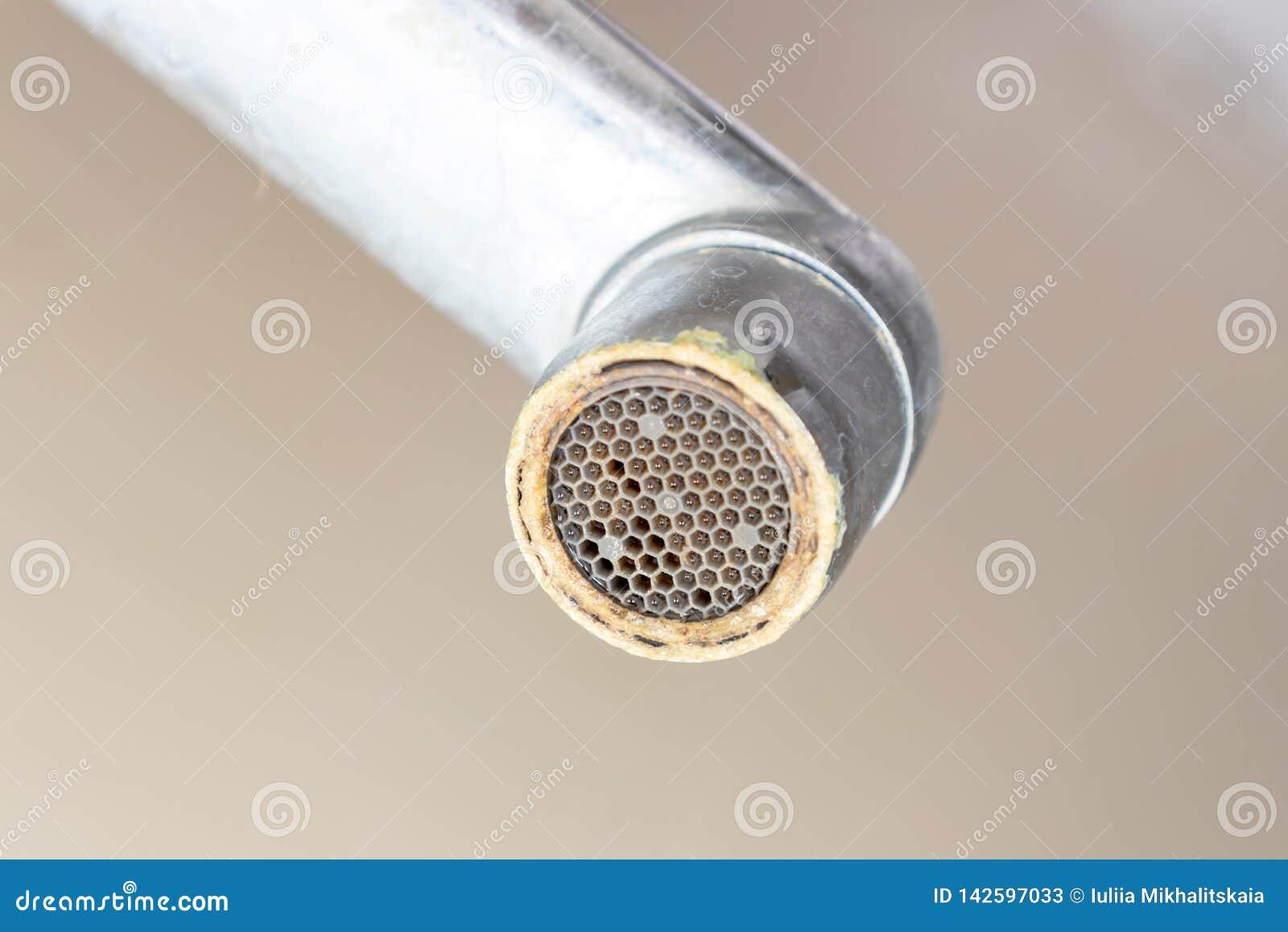 Smutsig vattenkranaerator med limescale, förkalkat duschvattenklapp med limefruktskalan i badrummet, slut upp