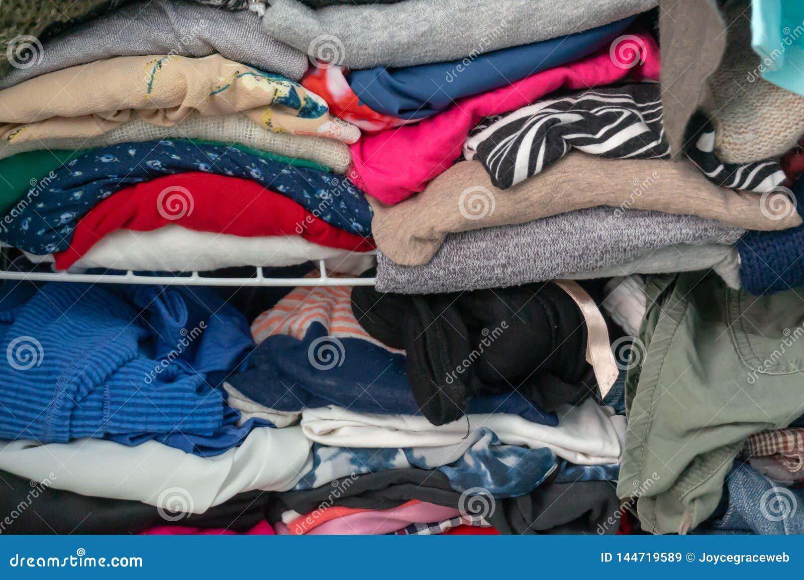 Smutsig vikt kläder som proppas i en garderob på en hylla Visa upp kvinnas garderob, consumerism, lokalvård och att ordna och